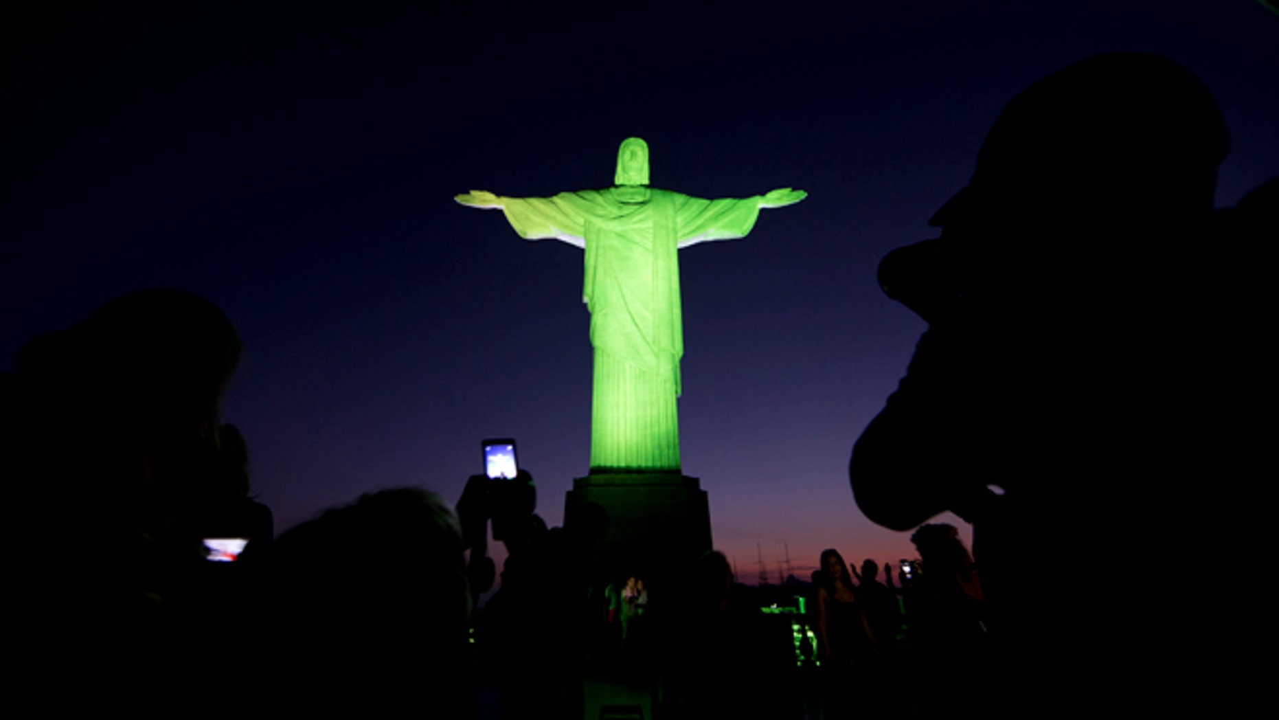 Christ the Redeemer statue is illuminated in green and yellow, the colors of the Brazil's flag, to celebrate the Summer Olympic Games, in Rio de Janeiro, Brazil, Thursday, Aug. 4, 2016. (AP Photo/Joao Laet)