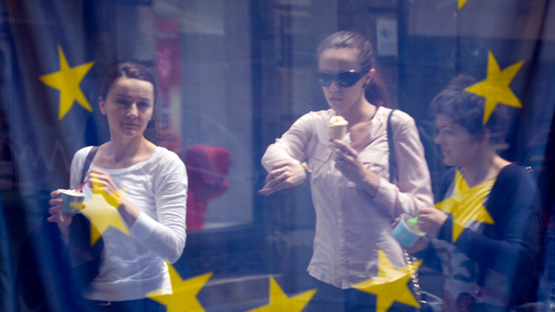 June 30, 2013: A street scene is reflected in the window of a library with an EU flag on display  in downtown  Zagreb, Croatia.
