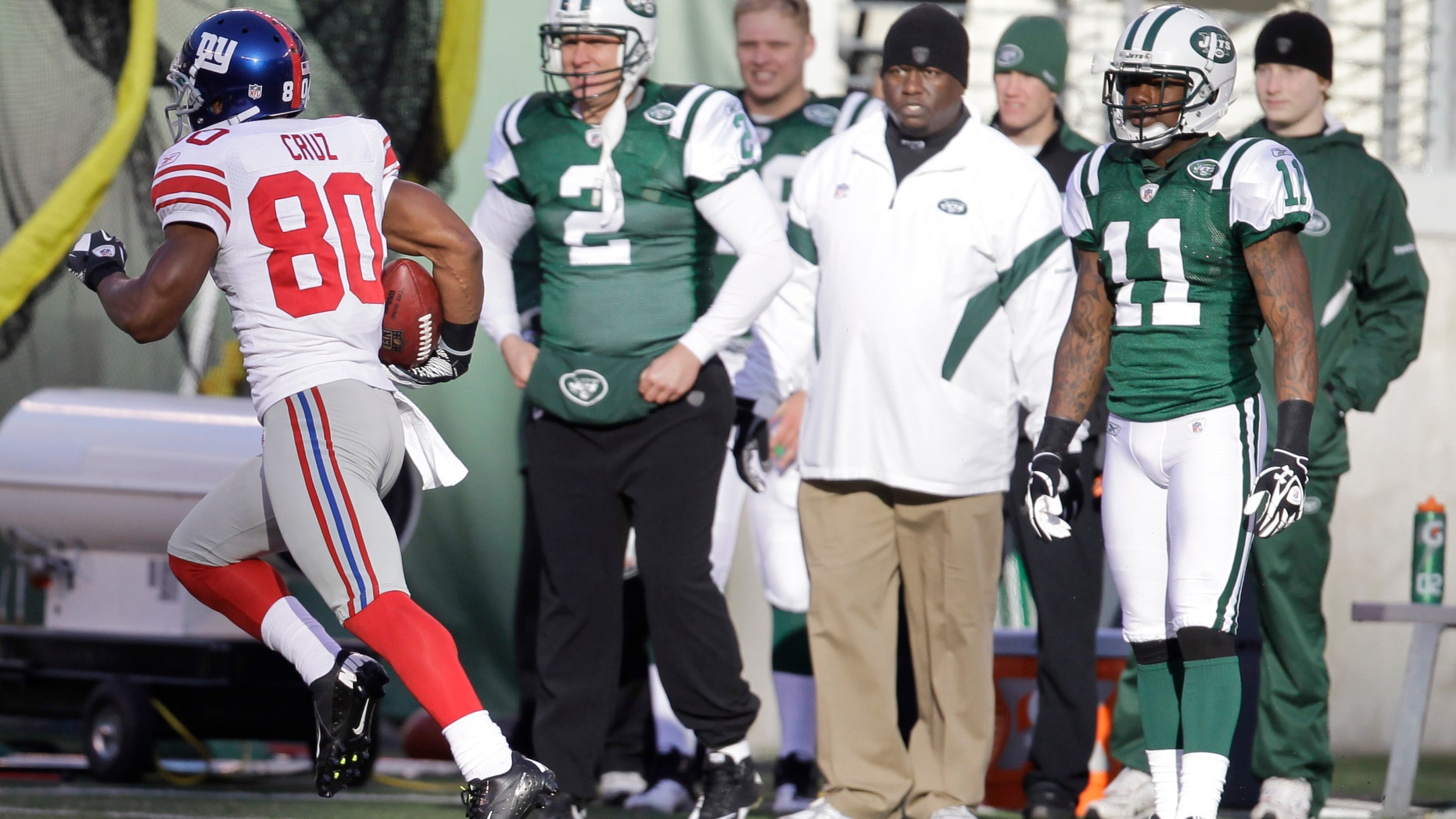New York Giants' Victor Cruz (80) runs 99 yards for a touchdown as the New York Jets sideline watches during the second quarter of an NFL football game between the New York Giants and the New York Jets, Saturday, Dec. 24, 2011, in East Rutherford, N.J. (AP Photo/Julio Cortez)