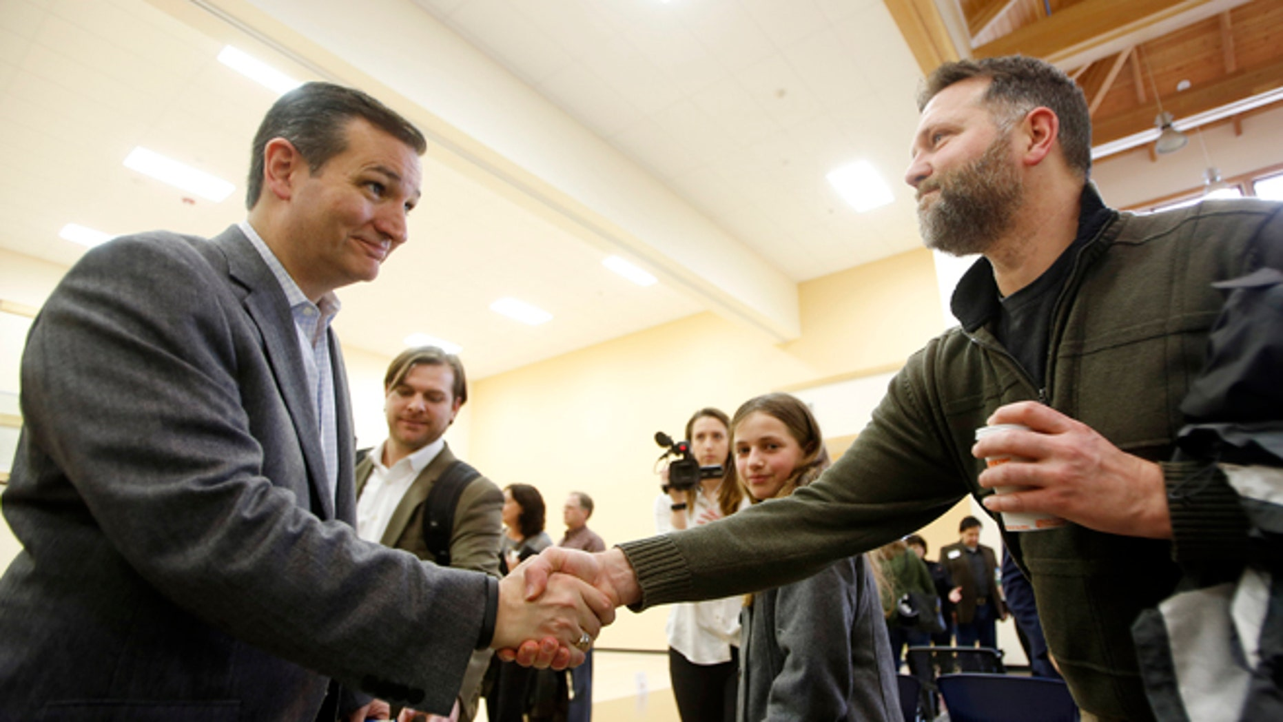 U.S. Sen. Ted Cruz, R-Texas, a tea party favorite and possible presidential candidate in 2016, left, shakes hands with Peter Smith during a visit to the Strafford County Republican Committee Chili and Chat on Sunday, March 15, 2015, in Barrington, N.H. (AP Photo/Jim Cole)