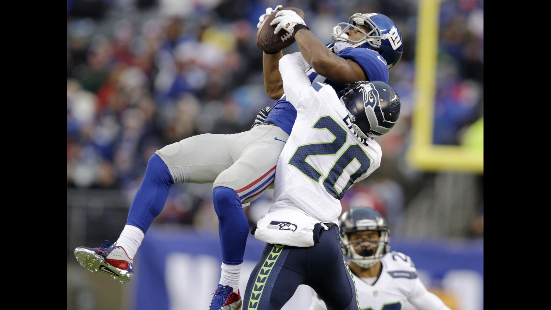 New York Giants wide receiver Victor Cruz, left, makes a catch as Seattle Seahawks cornerback Jeremy Lane defends on the play during the second half of an NFL football game, Sunday, Dec. 15, 2013, in East Rutherford, N.J. Cruz was banged up on the play and left the game with an injury. (AP Photo/Kathy Willens)