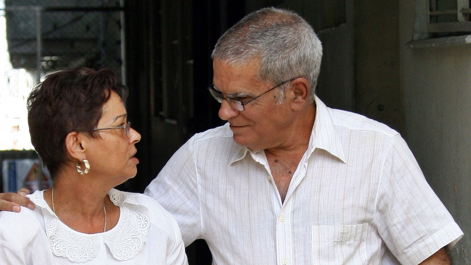 FILE - In this Nov. 29, 2004 file photo, Oscar Espinosa Chepe walks with his wife Miriam Leiva at their home after being freed on parole from prison where he was serving a twenty-year sentence, in Havana, Cuba.  Due to serious liver problems, Espinosa Chepe has been on an intravenous drip at a Havana hospital for more than a week, as of Monday, Sept. 3, 2012, and unable to even drink liquids until Monday morning, according to his wife Miriam Leiva, herself a leading dissident.  (AP Photo/Jose Goitia, File)