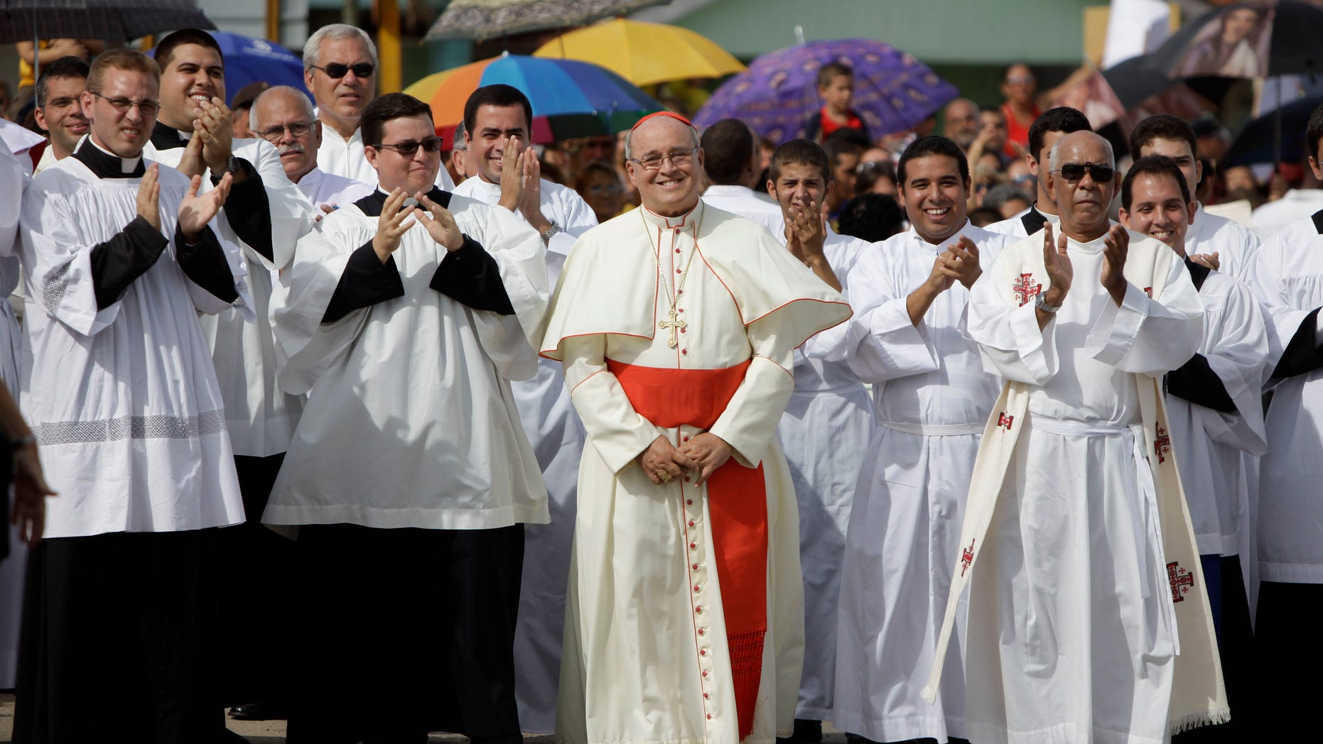 FILE - In this Sept. 4, 2011 file photo, Cuba's Cardinal Jaime Ortega, center, smiles as he waits for the Virgin of the Copper Charity during a procession in Madruga, Cuba. Ortega, who oversaw a warming of relations with the Communist government and played a role in the secret negotiations that led to U.S.-Cuba detente, has stepped down, the Vatican said on Tuesday, April 26, 2016. (AP Photo/Javier Galeano, File)