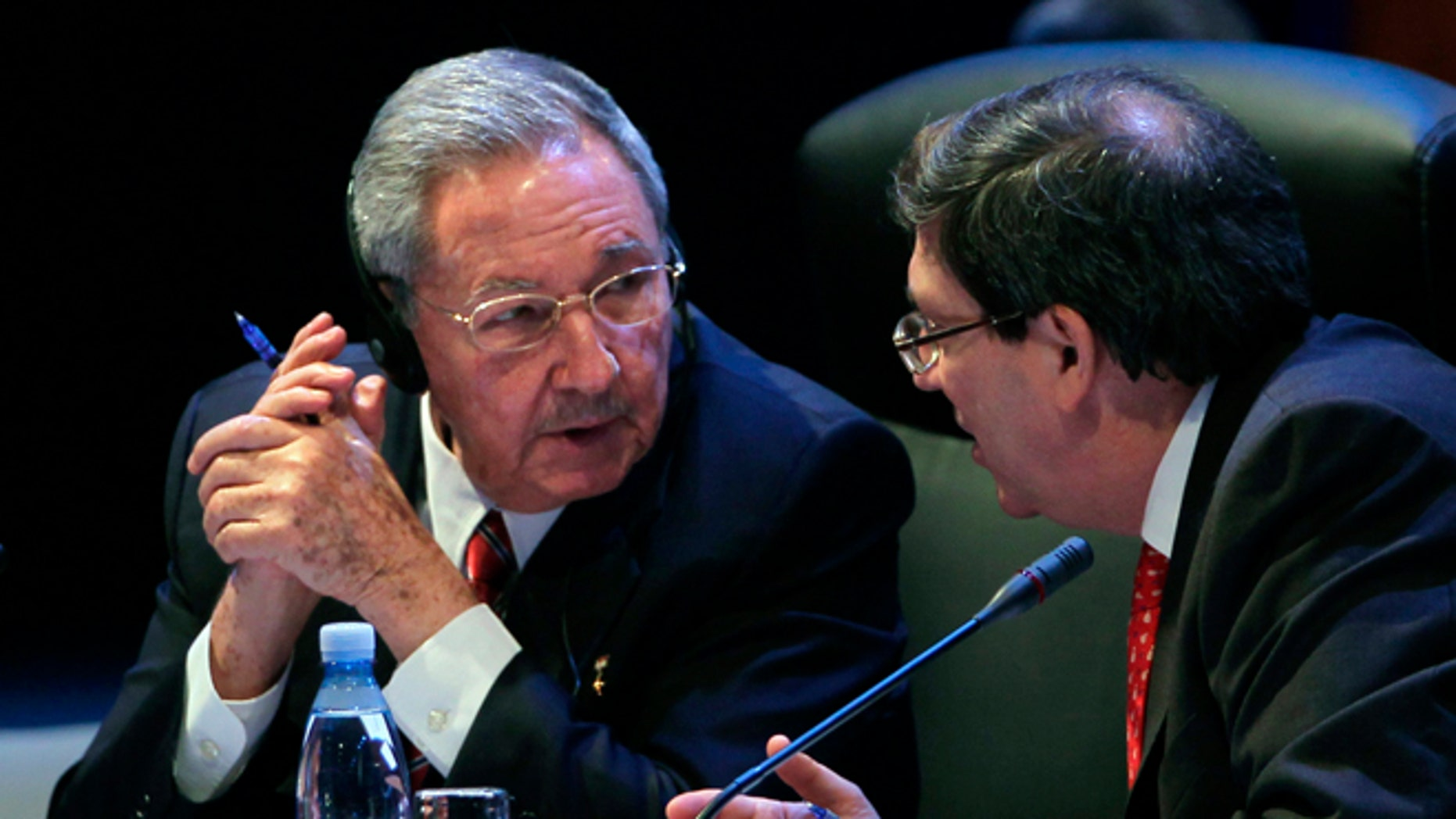 Cuba's President Raul Castro speaks to his Foreign Minister Bruno Rodriguez during a session of the CELAC Summit in Havana, Cuba, Tuesday, Jan. 28, 2014. Leaders from Latin America and the Caribbean are in Cuba to talk about poverty, inequality and hunger at the summit of the Community of Latin American and Caribbean States, or CELAC. (AP Photo/Cubadebate, Ismael Francisco)