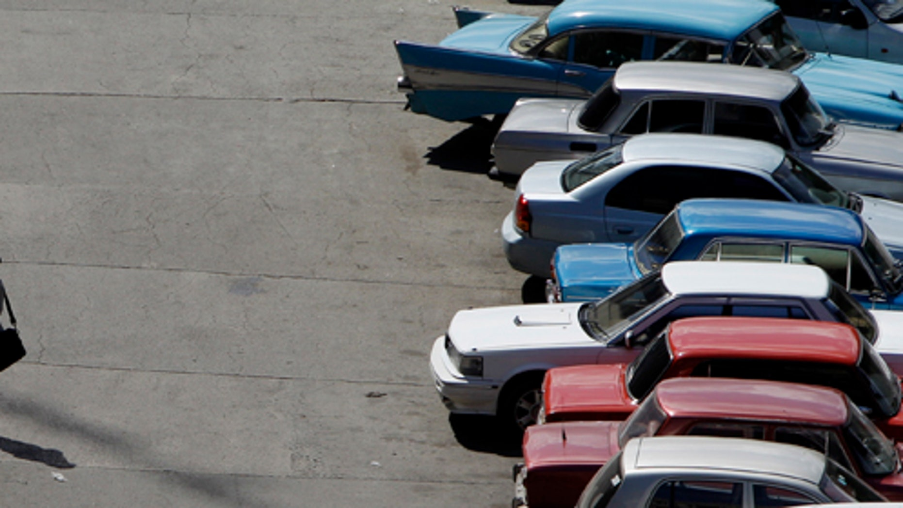 Sept 28: Two customs officers speak in a lot lined with cars in Havana, Cuba, The country  legalized the sale and purchase of automobiles for all citizens on Wednesday.
