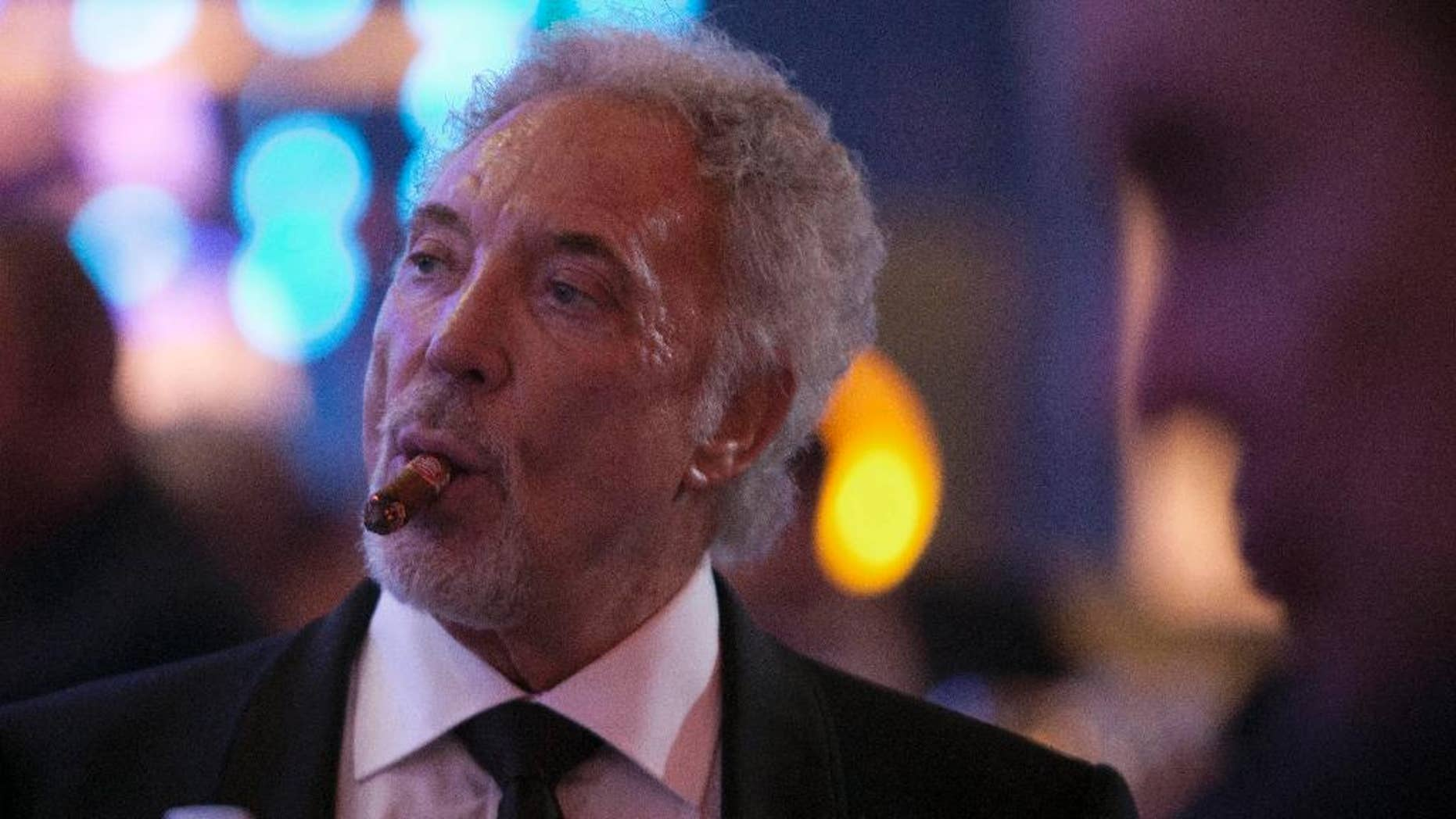 """Welsh crooner Tom Jones smokes a cigar during a gala dinner marking the end of the 16th annual Cigar Festival in Havana, Cuba, Friday, Feb. 28, 2014. The festival is a five-day bash that brings together hundreds of cigar sophisticates from around the world, and culminates with a gala and auction of humidors worth hundreds of thousands of dollars. Tom Jones was among the celebrity invitees at Saturday's auction and sang three songs for attending guests, including his signature """"It's Not Unusual.""""(AP Photo/Franklin Reyes)"""