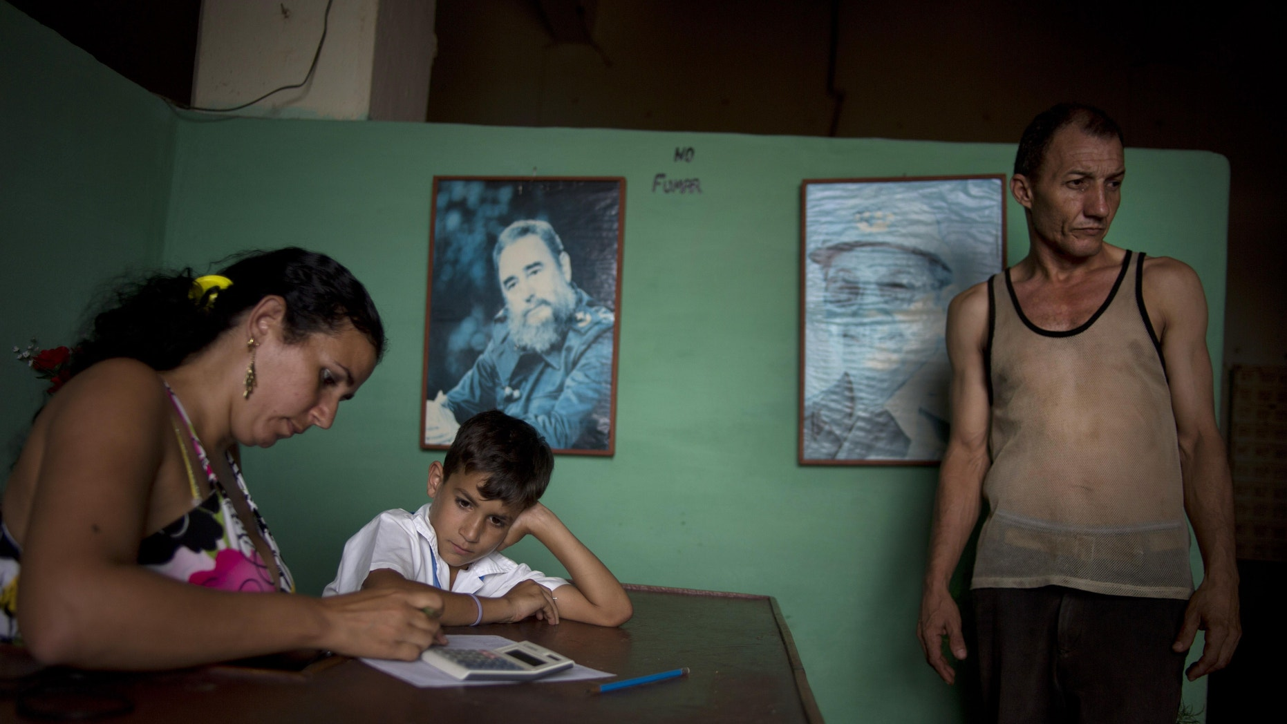 A worker, right, leaves the tobacco factory as a child waits for his mother to finish at a warehouse in the western province of Pinar del Rio, Cuba, Tuesday, Feb. 25, 2014. Pictures of Cuba's Fidel Castro and Raul Castro hang on the wall. Cigar enthusiasts from around the world come to Cuba during the annual Cigar Festival to visit tobacco farms and factories and savor new cigar brands. (AP Photo/Ramon Espinosa)