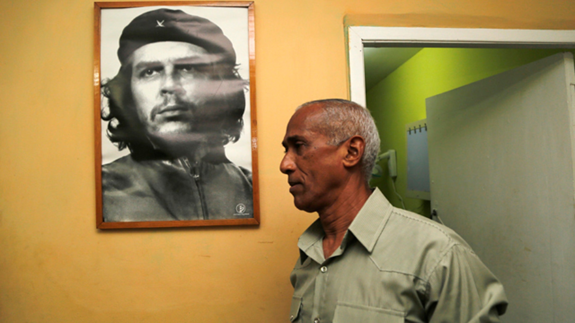 April 19, 2015: Dissident and candidate Hildebrando Chaviano walks beside a portrait of revolutionary leader Che Guevara before casting his ballot during Cuba's municipal elections at a polling station in Havana. (AP Photo/Desmond Boylan)