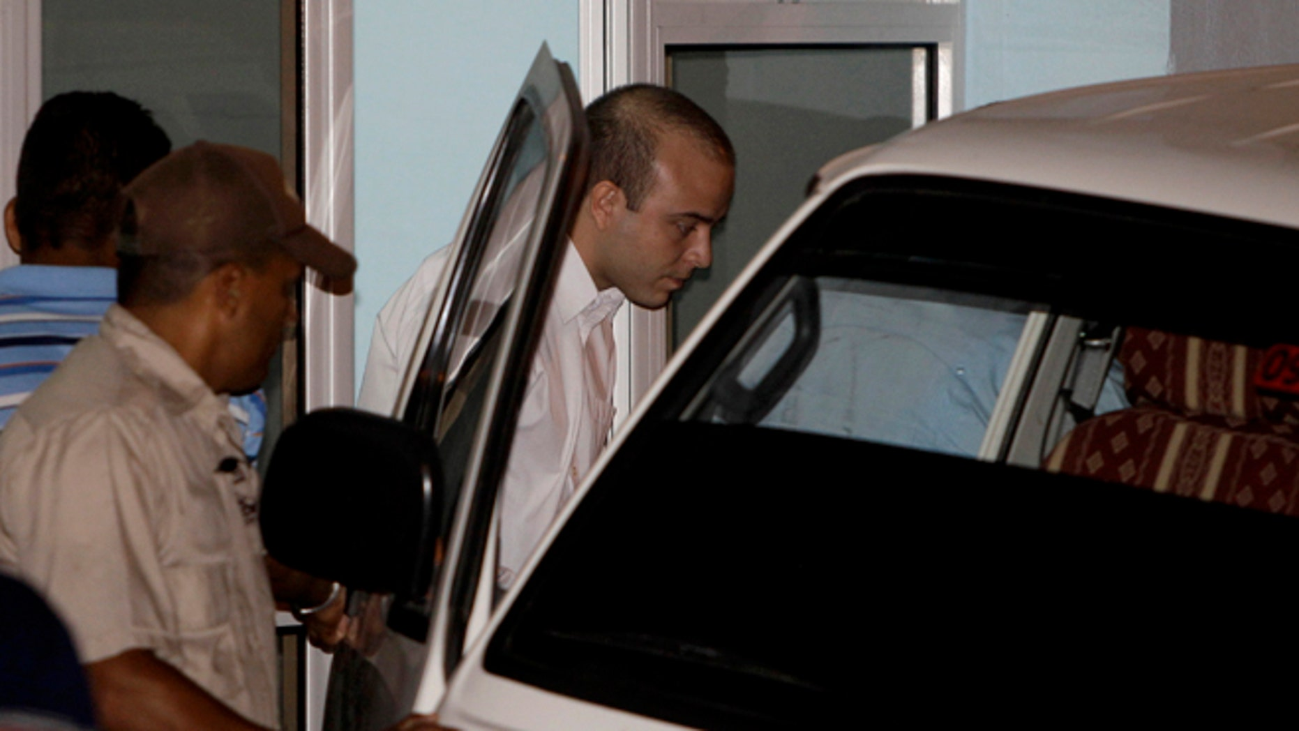 Spanish citizen Angel Carromero, center, enters a vehicle as he leaves the courthouse after his trial in Bayamo, Cuba, Friday, Oct. 5, 2012. Authorities accused Carromero of speeding and charged him with the equivalent of vehicular manslaughter, and prosecutors asked the court for a seven-year sentence. The car crash killed a prominent Cuban dissident Oswaldo Paya and another dissident, Harold Cepero on July 22.  A panel of judges will now consider the evidence and issue a ruling at an unspecified future date. (AP Photo/Franklin Reyes)