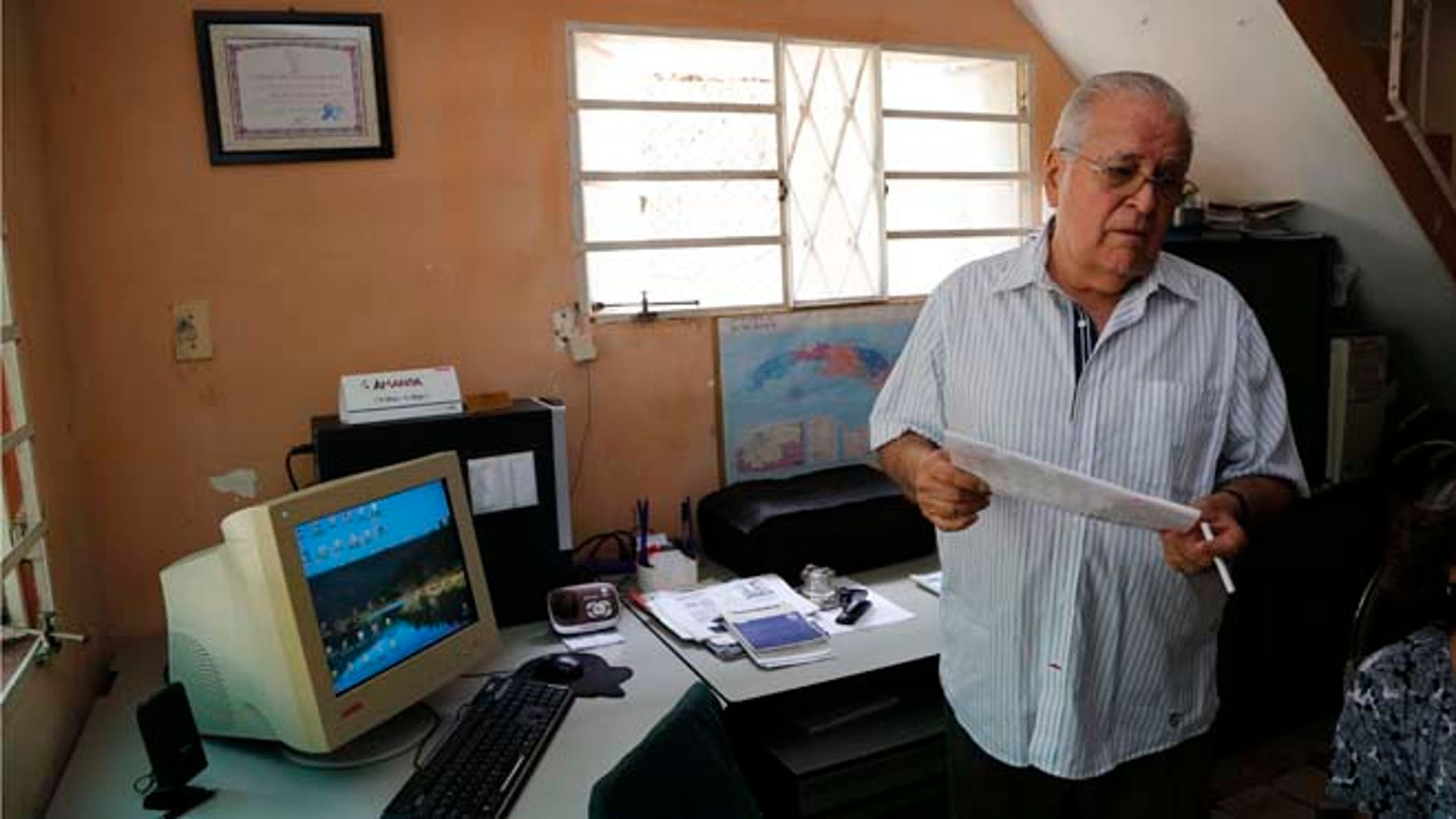 In this July 2, 2015 photo, dissident Elizardo Sanchez, president of the Cuban Commission for Human Rights and National Reconciliation, stands in his home in Havana, Cuba. Many of the dissidents are feeling increasingly sidelined and abandoned as both countries celebrate milestones like Monday's opening of embassies in Havana and Washington. (AP Photo/Desmond Boylan)