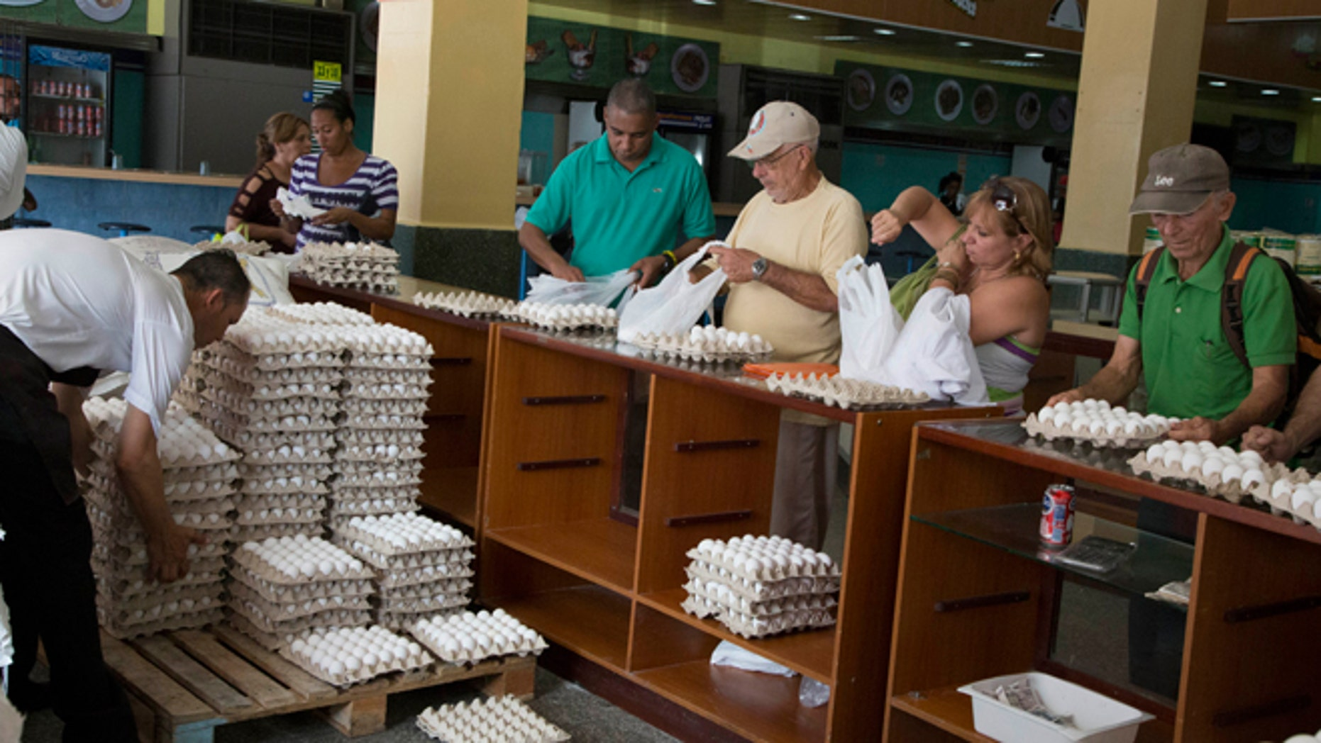 People buy eggs at a a store in Havana, Cuba, Friday, March 20, 2015. More than a dozen Cuban officials have been sentenced to between five and 15 years in prison in connection with what authorities call a scheme to divert millions of eggs to the black market. (AP Photo/Desmond Boylan)