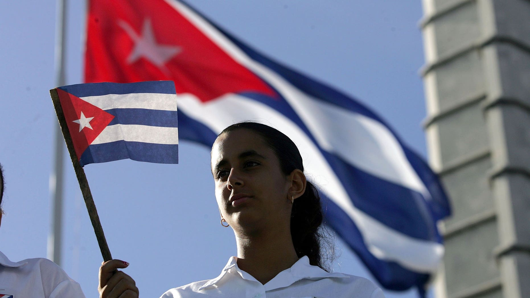HAVANA, CUBA - DECEMBER 02:  A young women waves a Cuban flag in Havana's Revolution Square during the 50th anniversary celebration of the forming of Cuba's Revolutionary Armed Forces December 2, 2006 in Havana, Cuba. Many in the crowd were hoping to catch a glimpse of Cuban President Fidel Castro who did not attend the parade.  (Photo by Joe Raedle/Getty Images)