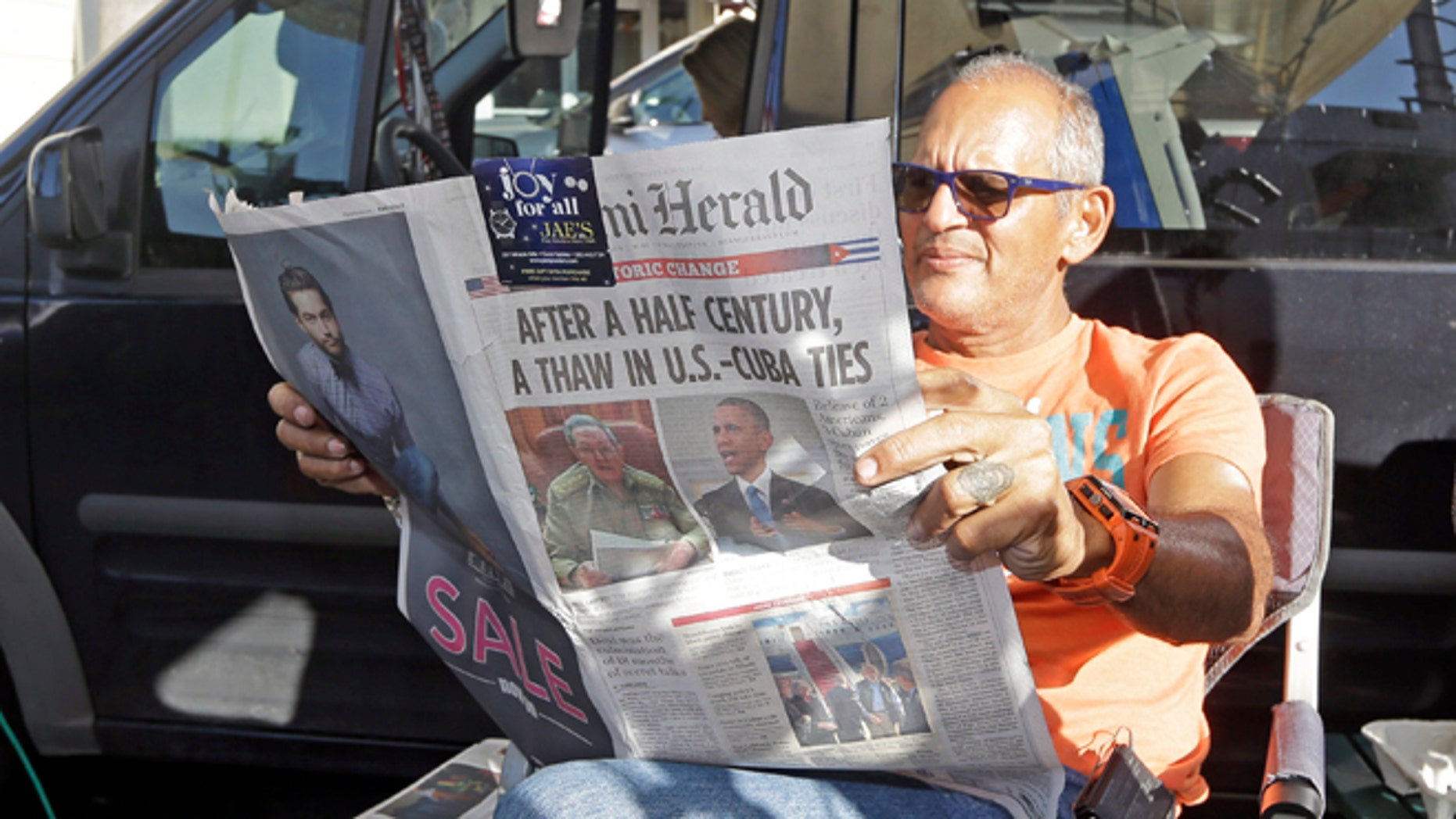 MSNBC photographer Tony Zumbado reads the Miami Herald in the Little Havana area of Miami, Thursday, Dec. 18, 2014, as news agencies from all over the world prepare to cover the reaction of the Cuban-Americans to the surprising move by President Barack Obama to restore the nation's ties with Cuba.  The U.S. and Cuba will begin taking steps to restore full diplomatic relations, marking the most significant shift in U.S. policy toward the communist island in more than half a century. (AP Photo/Alan Diaz)
