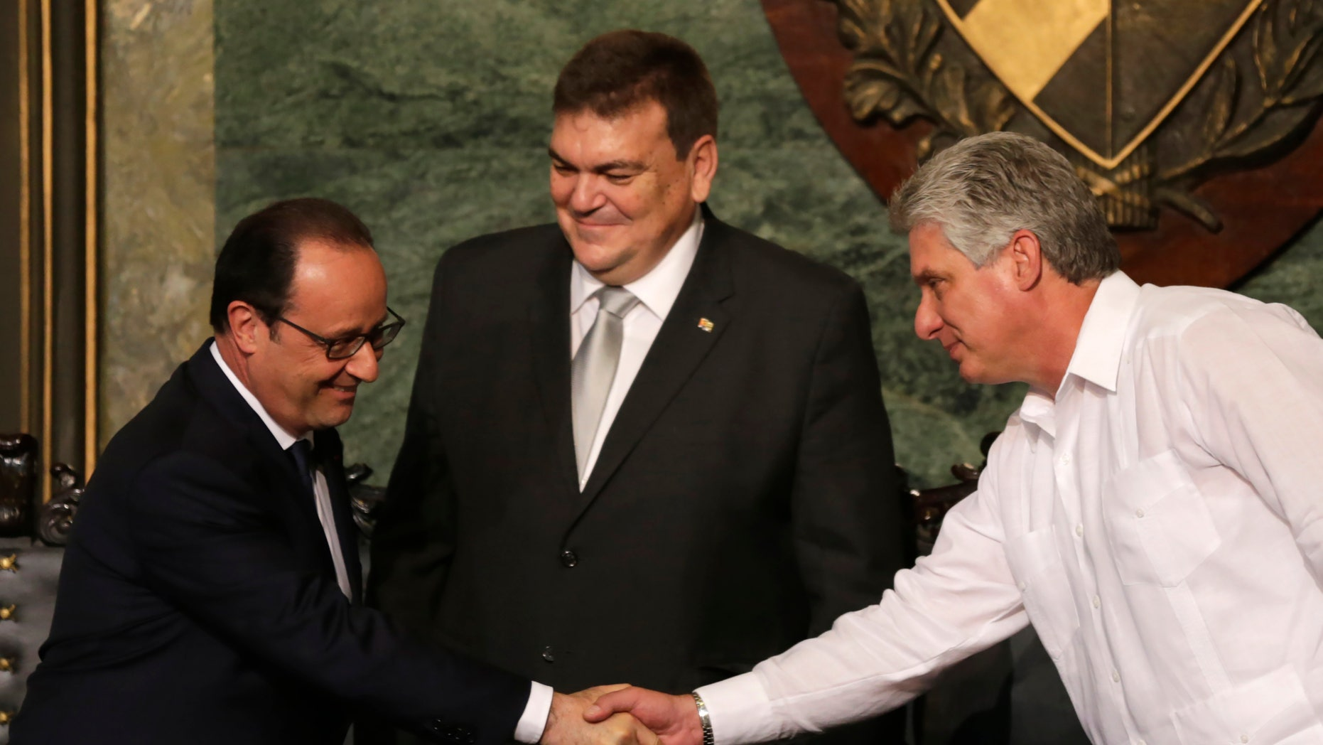 French President Francois Hollande shakes hands with Cuba's Vice President Miguel Diaz-Canel, right, in front of Gustavo Cobreiro, University Havana rector, in Havana, Cuba, Monday, May 11, 2015. Accompanied by a group of top  French business people, Hollande has become the first French president to visit Cuba since it became an independent country, using a one-day trip to build business and diplomatic relations five months after a detente between Havana and Washington.(AP Photo/Desmond Boylan)