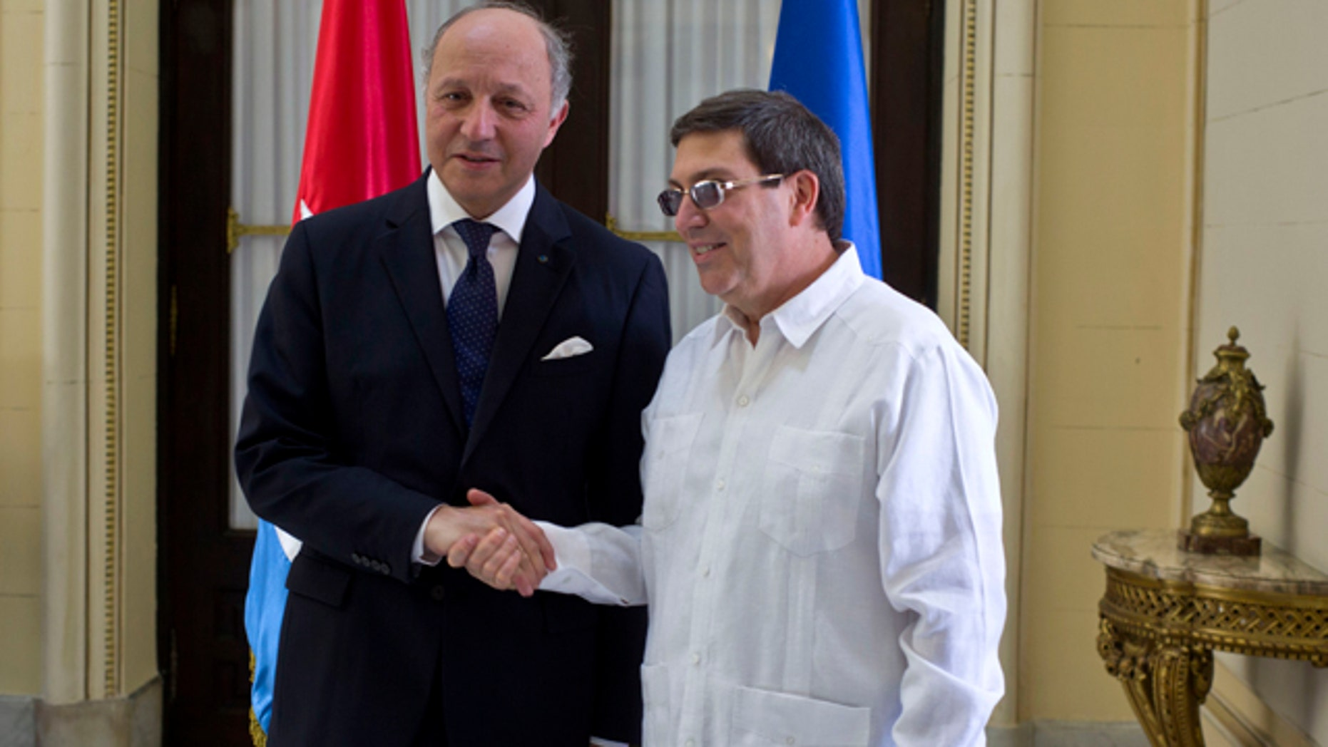 April 12, 2014: Cuba's Foreign Minister Bruno Rodriguez, right, and France's Foreign Minister Laurent Fabius shake hands toward photographers prior to their meeting at the Foreign Ministry in Havana, Cuba. (AP Photo/Ramon Espinosa)