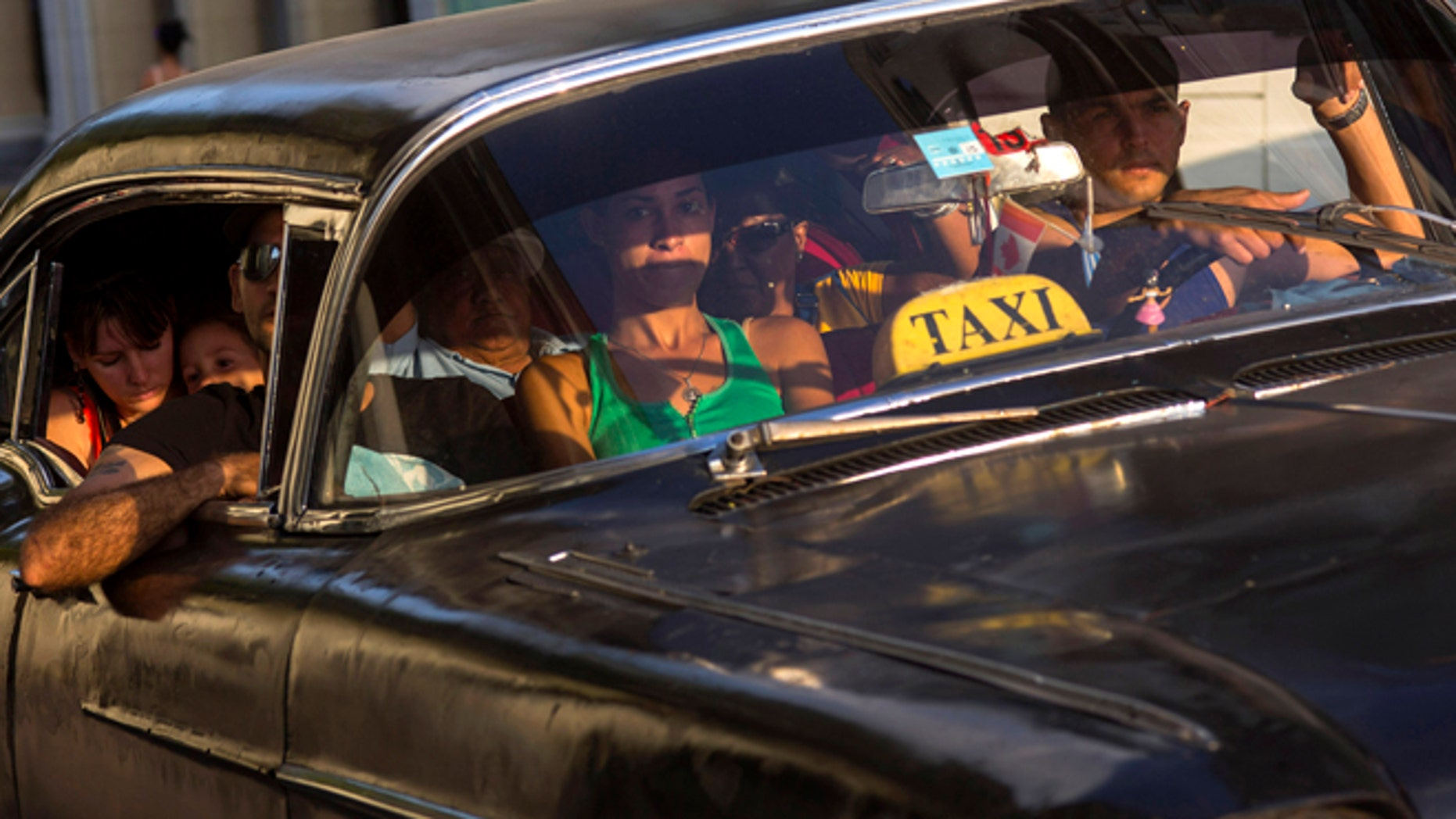 A taxi driver transports a car full of passengers, in Havana, Cuba, Tuesday, Feb. 17, 2015. A more relaxed and hopeful atmosphere is evident in Cuba as a result of President Raul Castroís modest reforms and afte the agreement by Cuba and the U.S. to move toward a more normal relationship. (AP Photo/Ramon Espinosa)