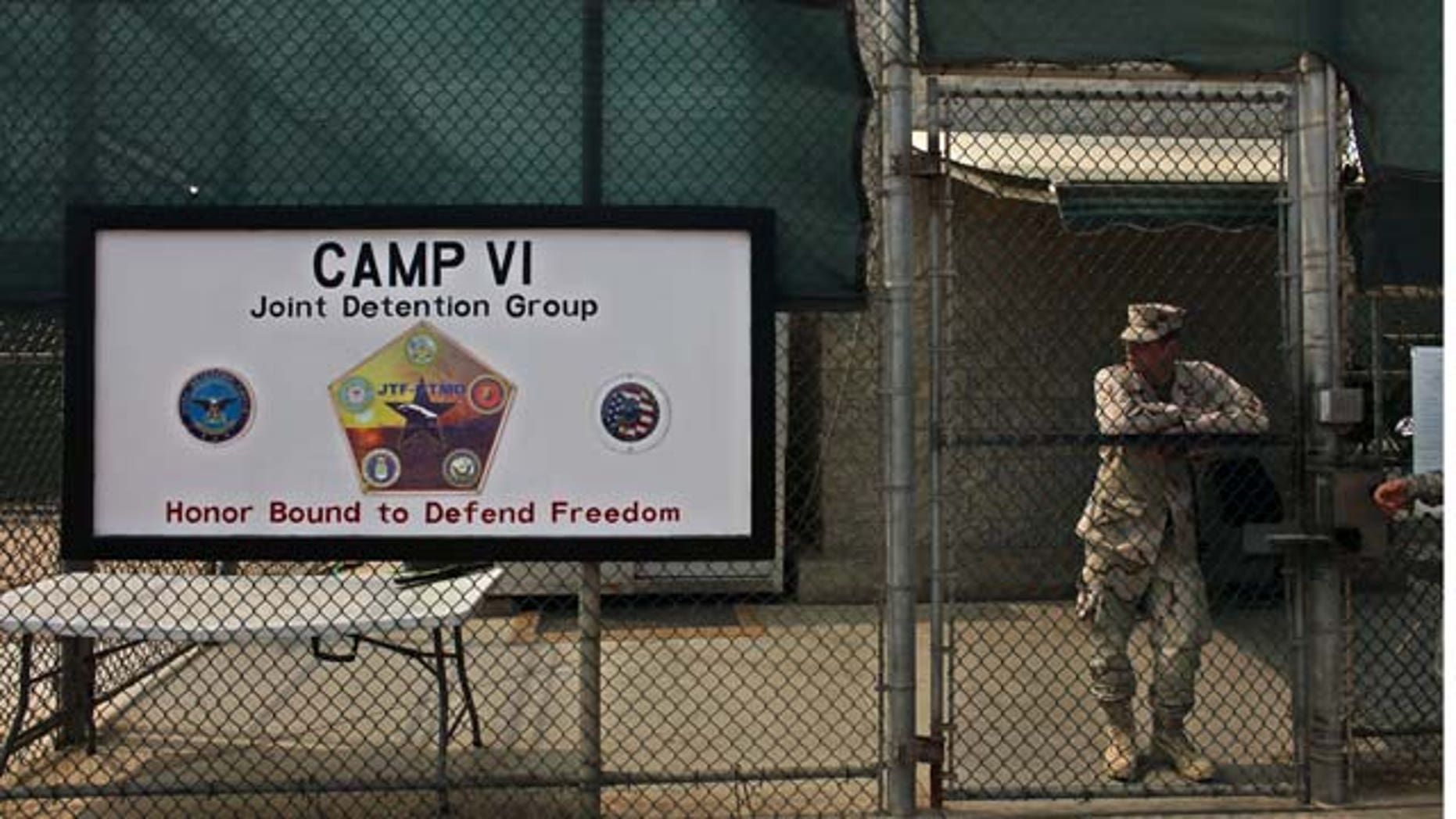 In this file photo taken Tuesday May 12, 2009 and reviewed by the U.S. military, a soldier stands guard at the front gate entrance to the Camp 6 maximum-security detention facility, at Guantanamo Bay U.S. Naval Base, Cuba. (AP)