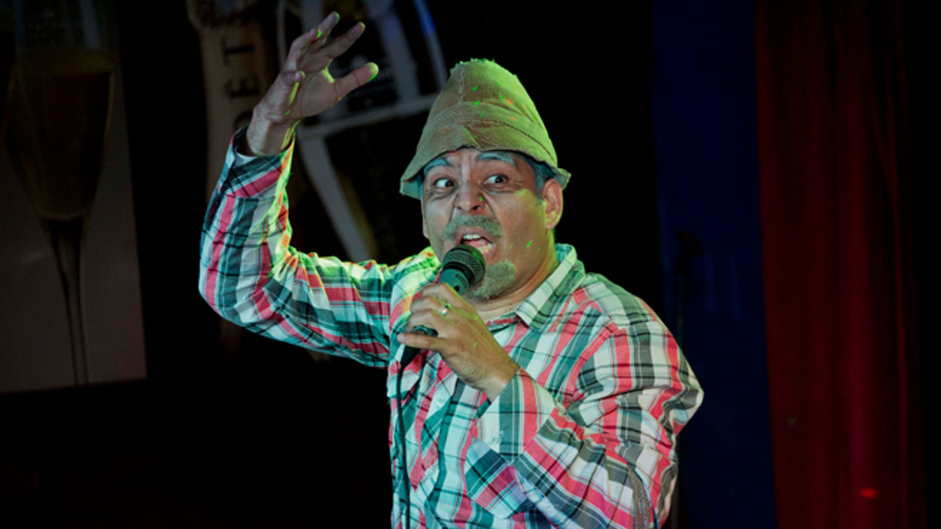 """Cuban actor Luis Silva whose stage name is """"Panfilo"""" performs in front of  the public in Havana, Cuba, Monday, Dec. 8, 2014. The comedian's jokes resonate deeply with Cubans frustrated by petty corruption, scarcity of many goods, and the poor quality of even the most basic staples. (AP Photo/Desmond Boylan)"""