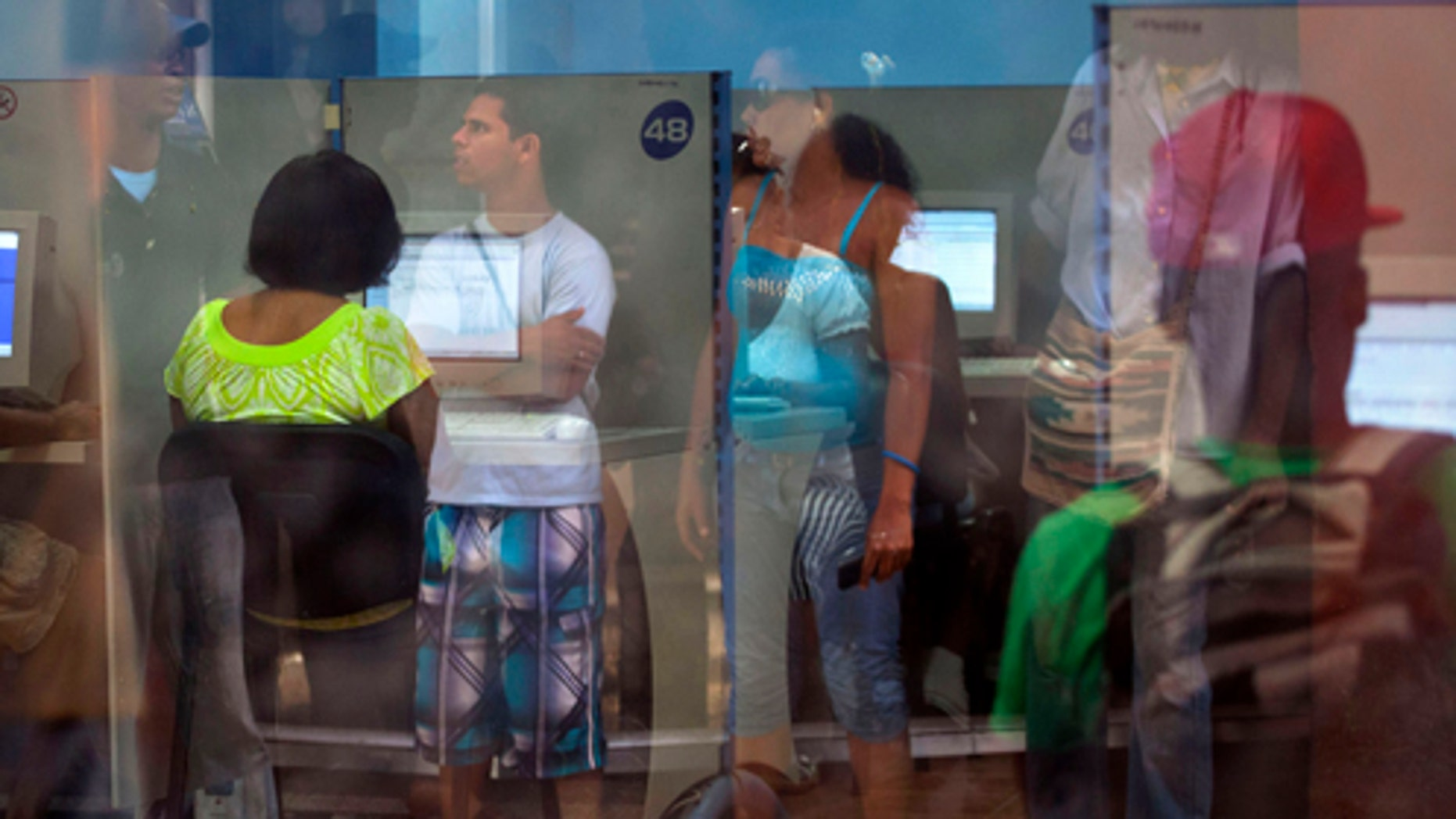 People reflected in the window line up at a post office as they wait to use the Internet service in Havana, Cuba, Tuesday, May 28, 2013. Cuba announced Tuesday that it will offer more access to the Internet starting June 4, at navegation sites around the country for $4.50 an hour. The average salary in Cuba is $15 per month. (AP Photo/Ramon Espinosa)