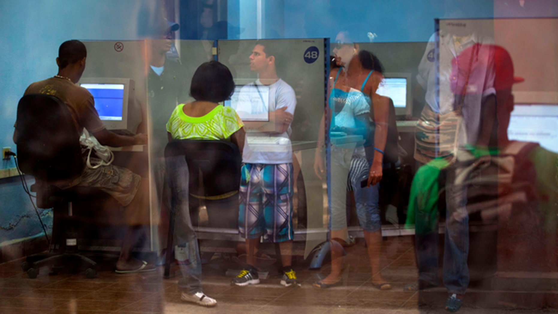 People line up at a post office as they wait to use the Internet service in Havana, Cuba, Tuesday, May 28, 2013.