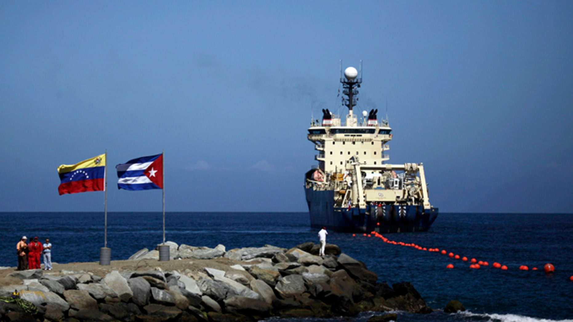 Jan. 22, 2011: {eople stand on a breakwater, with a Venezuelan flag, left, and a Cuban flag, as a specialized ship rolls out a fiber-optic cable, suspended from buoys, off La Guaira, Venezuelan coast. Cuba's state telecom monopoly confirmed Thursday, Jan. 24, 2013 that the island's first hard-wired Internet connection to the outside world has been activated, but said it won't lead to an immediate increase in access.