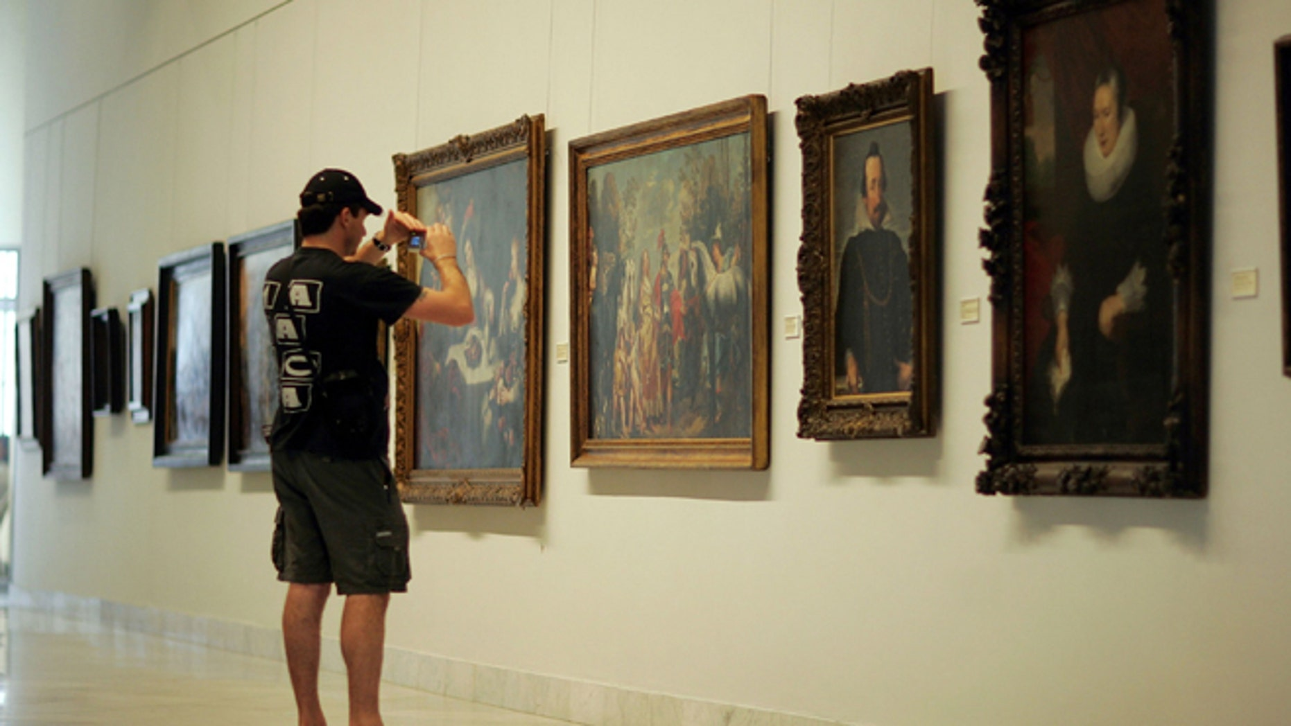 HAVANA - DECEMBER 01: A visitor photographs the paintings on display at the Fine Arts Museum December 1, 2006 in Havana, Cuba. (Photo by Joe Raedle/Getty Images)