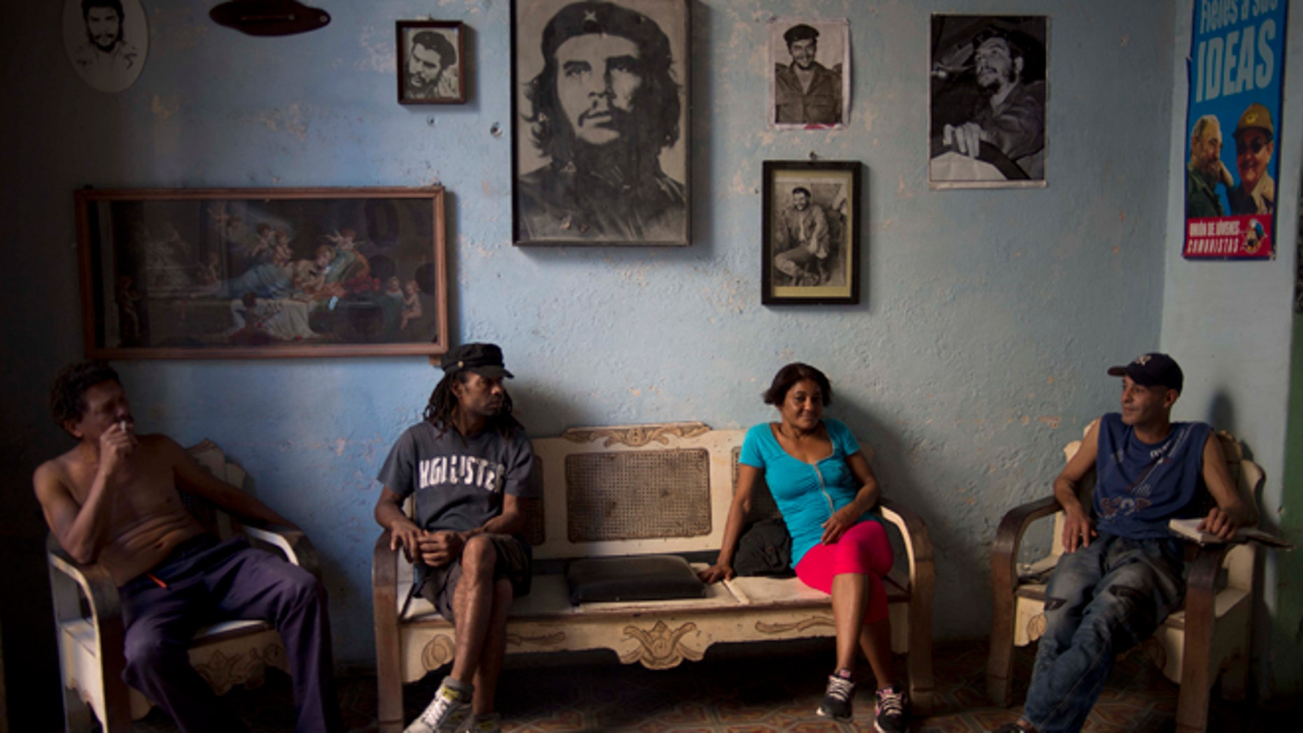 Roberto Alvarez, 47, right, chats with friends backdropped by a wall decorated with images of Cuban revolutionary heroes, Che Guevara, Fidel Castro and his brother, President Raul Castro, in Havana, Cuba, Wednesday, Feb. 25, 2015. Any kind of benefit for the Cuban people, thatll be hard. said Alvarez when asked if the negotiations with the US would help. (AP Photo/Ramon Espinosa)