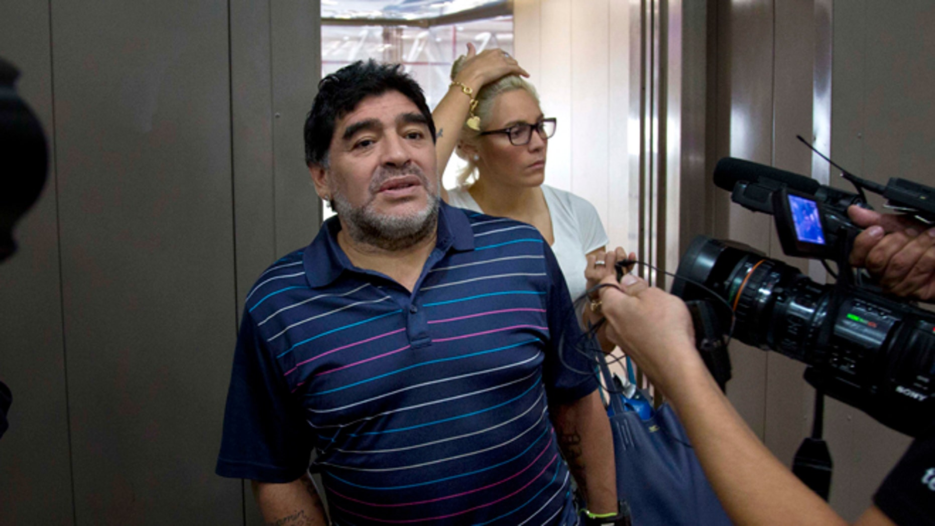 Argentina's soccer legend Diego Armando Maradona talks to journalists at the airport on his way to catch a departing plane in Havana, Cuba, Monday, Jan. 12, 2015. Behind is his girlfriend Rocio Oliva. Fidel Castro on Monday sent Maradona a letter written to quash rumors of the Cuban leader's death, state-run television network Telesur reported. It was the first reported word from Castro in nearly three months. The network showed photos of Maradona with the letter signed by Castro, 88. Telesur revealed nothing about the contents of the letter, but said it rebutted rumors he had died. (AP Photo/Ramon Espinosa)