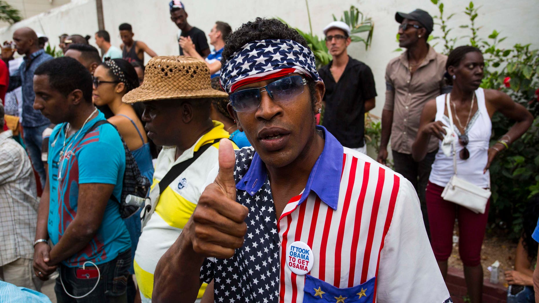 A man wearing a shirt and head scarf with a Stars and Stripes motif flashes a thumbs up at a weekly rumba dance gathering in Havana, Cuba, Saturday, March 19, 2016. President Barack Obama will travel to the communist island March 20. During his three-day trip, the first to the country by a sitting president in nearly 90 years he will meet with President Raul Castro at the Palace of the Revolution and attend a baseball exhibition game. (AP Photo/Desmond Boylan)