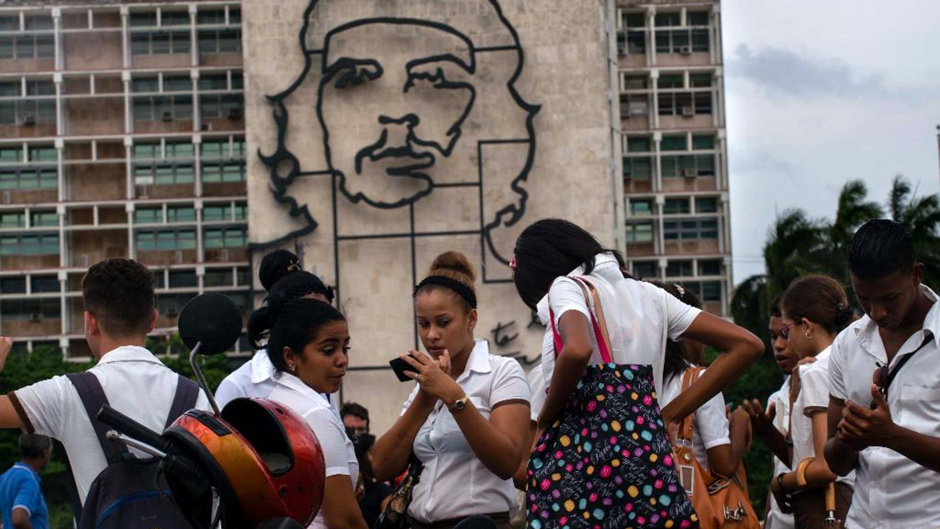 """Students stand in Revolution Square next to the sculpture of revolutionary hero Ernesto """"Che"""" Guevara, where the Pope Francis will give a Mass next Sunday in Havana, Cuba,Thursday, Sept. 17, 2015. (AP Photo/Ramon Espinosa)"""