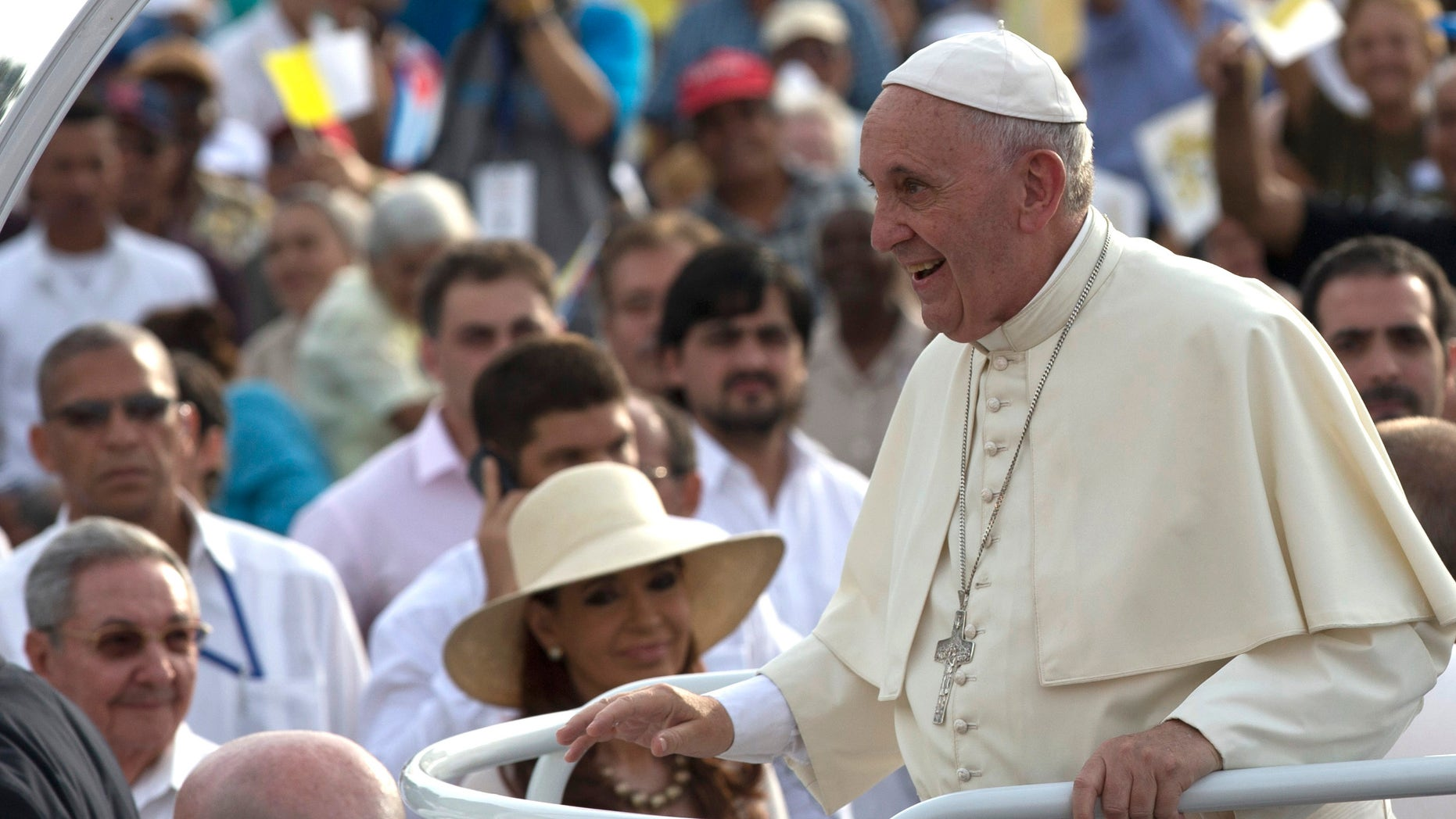 Cuba's President Raul Castro, behind left, and Argentina's President Christina Fernandez, in hat, watch Pope Francis arrive for Mass at Revolution Plaza in Havana, Cuba, Sunday, Sept. 20, 2015.  Pope Francis opens his first full day in Cuba on Sunday with what normally would be the culminating highlight of a papal visit: Mass before hundreds of thousands of people in Havana's Revolution Plaza. (Ismael Francisco/Cubadebate Via AP)