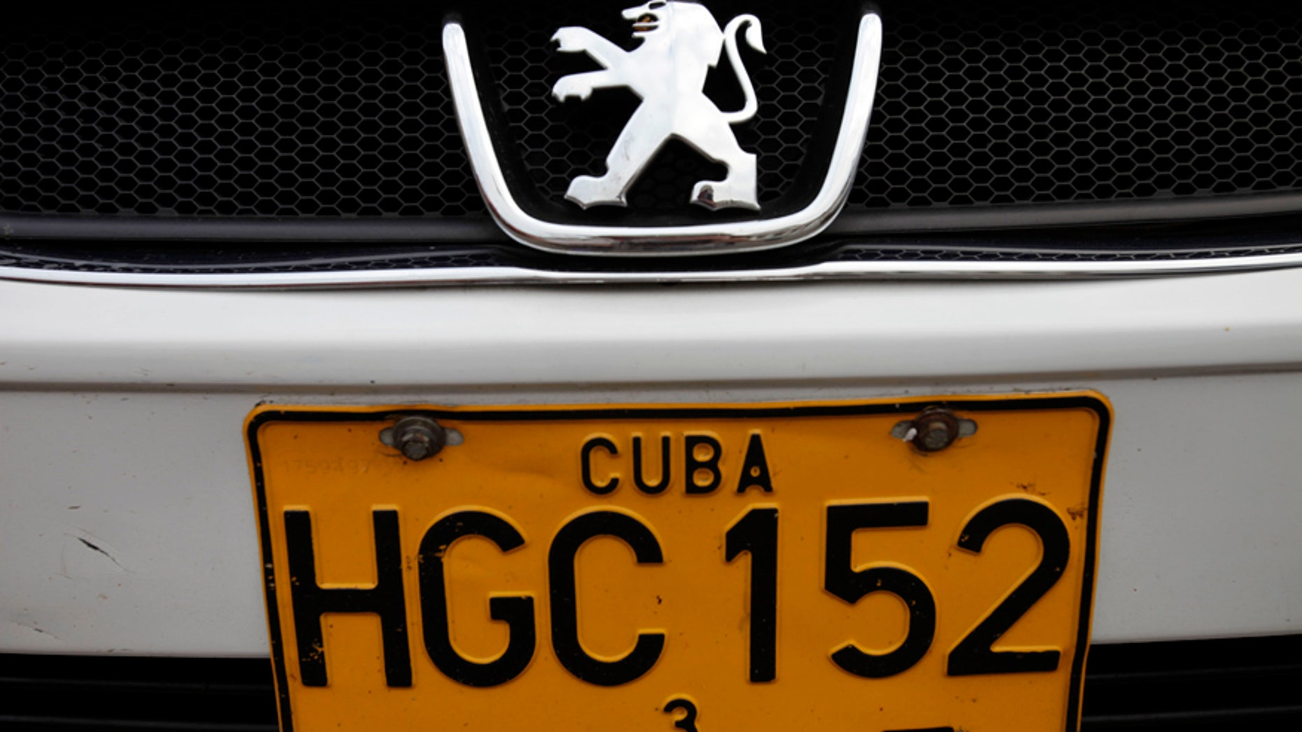 FILE - This Dec. 19, 2013 file photo shows a detail of a license plate on a Peugeot as it drives by in Havana, Cuba. Cuban authorities reported on Monday, June 30, 2014 that auto dealerships have sold just 50 automobiles and four motorcycles across the country in the nearly six months since a new law took effect letting islanders buy vehicles without a special permit for the first time in decades. Many Cubans were delighted when the new rules were announced in December 2013, and then left aghast by the sticker prices once they took effect. Most Cubans earn about $20 a month. (AP Photo/Franklin Reyes, File)