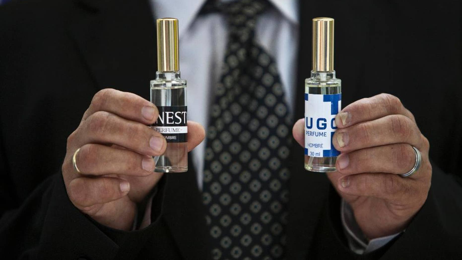 "A man shows two bottles of cologne, one called ""Ernesto,"" honors guerrilla leader Ernesto ""Che"" Guevara, and ""Hugo,"" for the late Venezuelan president Hugo Chavez, in Havana, Cuba, Wednesday, Sept. 24, 2014. Formulated by a French company and produced in Cuba, the colognes are being presented this week at a Labiofam convention in Havana. (AP Photo/Franklin Reyes)"