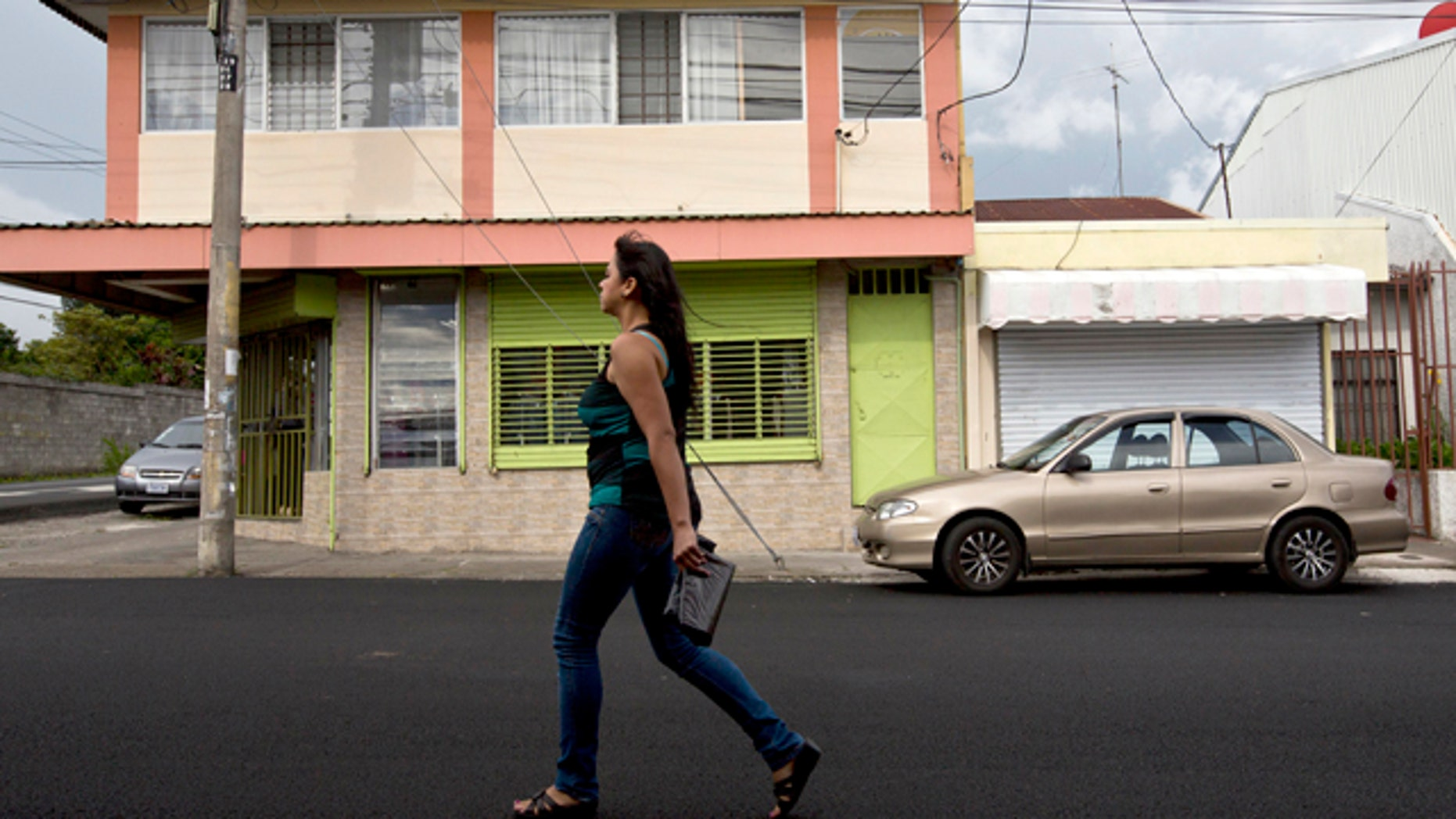 July 9, 2014: A woman walks in front of the building that once housed the human rights group Fundacion Operacion Gaya Internacional in Heredia, Costa Rica. (AP Photo/Esteban Felix)