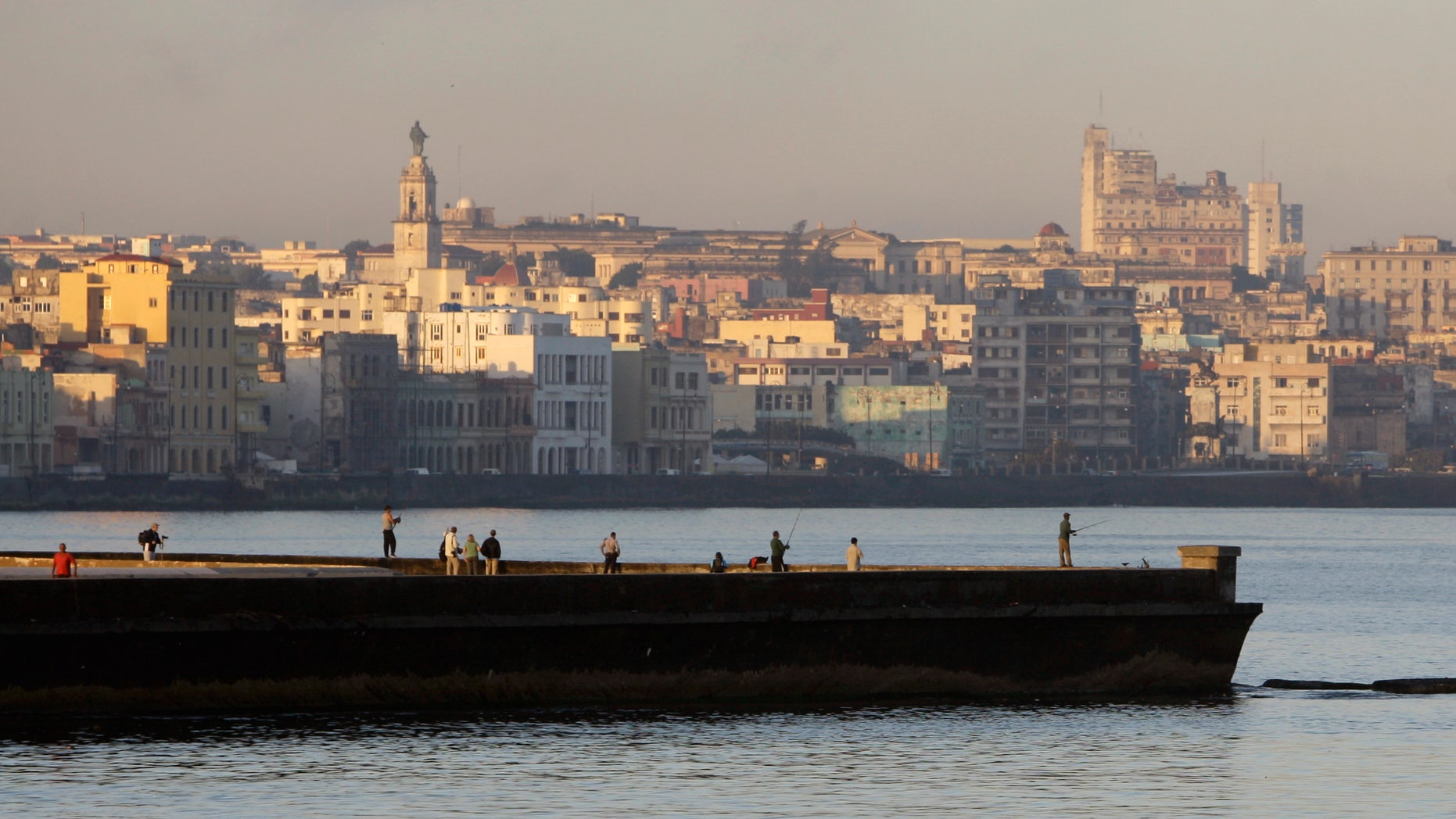 People fish from a dock in Havana Bay, Cuba, Tuesday Feb. 7, 2012. (AP Photo/Franklin Reyes)