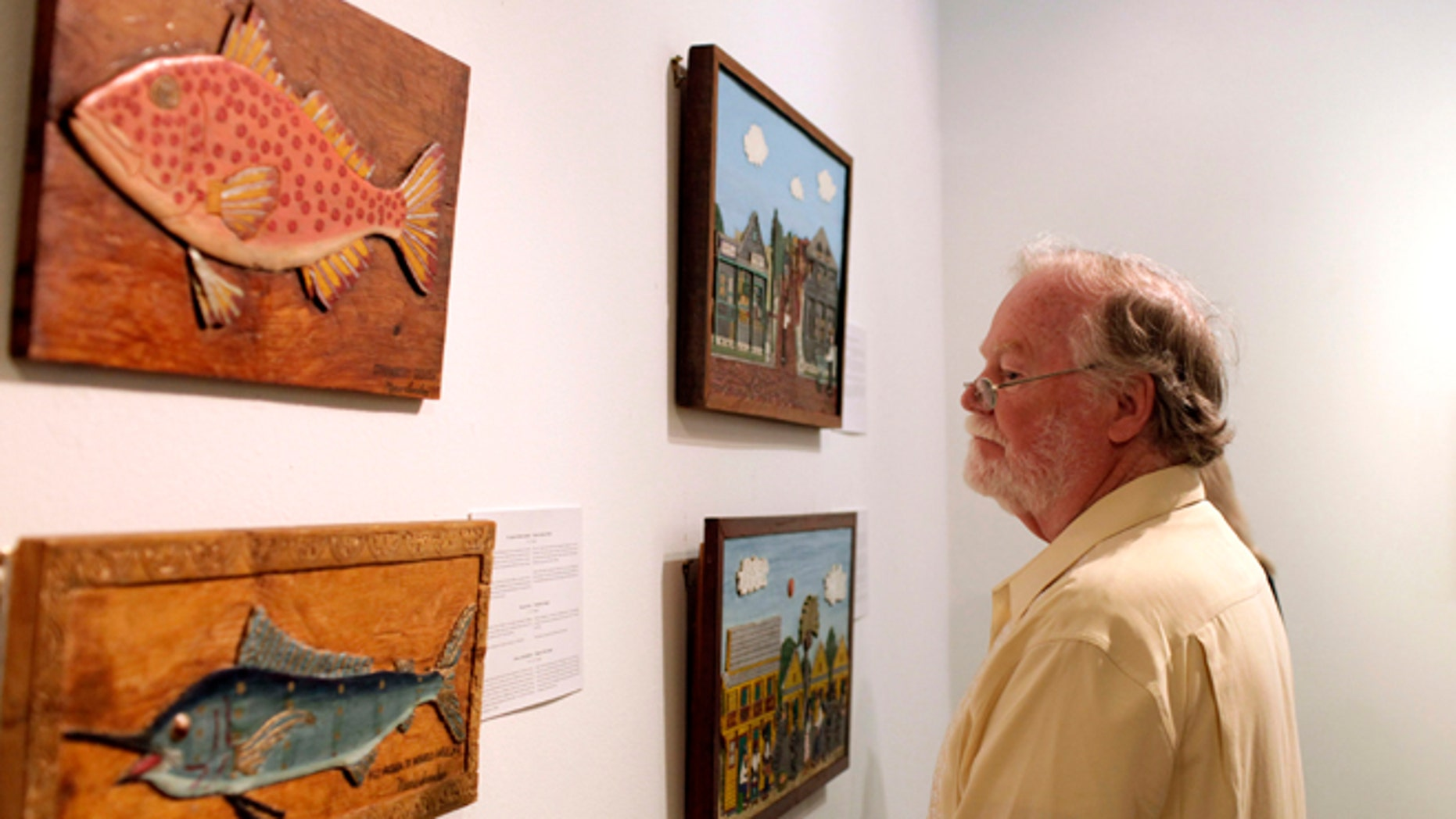 """A man looks at art by Mario Sanchez, a deceased Florida artist of Cuban descent, inside the Bellas Artes museum in Havana, Cuba, late Friday, Jan. 17, 2014. The show, titled """"Una Raza"""" or """"One Race,"""" is part of an exchange between Havana and Key West under which several prominent Cuban artists will exhibit on the Florida island next month. (AP Photo/Franklin Reyes)"""