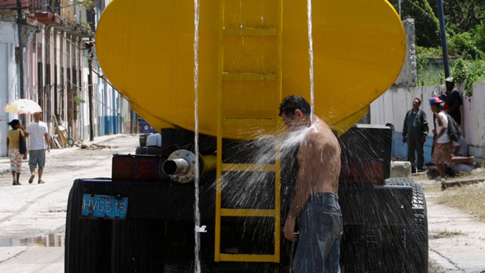 """A man cools himself in water overflowing from a parked truck that delivers drinking water in Havana, Cuba, Wednesday, Aug. 21, 2013. The United States has issued an advisory for travelers to Cuba after several foreign visitors were sickened by cholera in recent weeks. """"We urge you to follow public health recommendations and guidelines, such as safe food and water precautions and frequent hand washing to help prevent cholera infection,"""" the diplomatic mission said in a statement published online. The embargo against Cuba bars most American tourism to the island, but hundreds of thousands of Cuban-Americans make legal family visits each year and increasing numbers of U.S. citizens are visiting through licensed cultural exchanges. (AP Photo/Franklin Reyes)"""