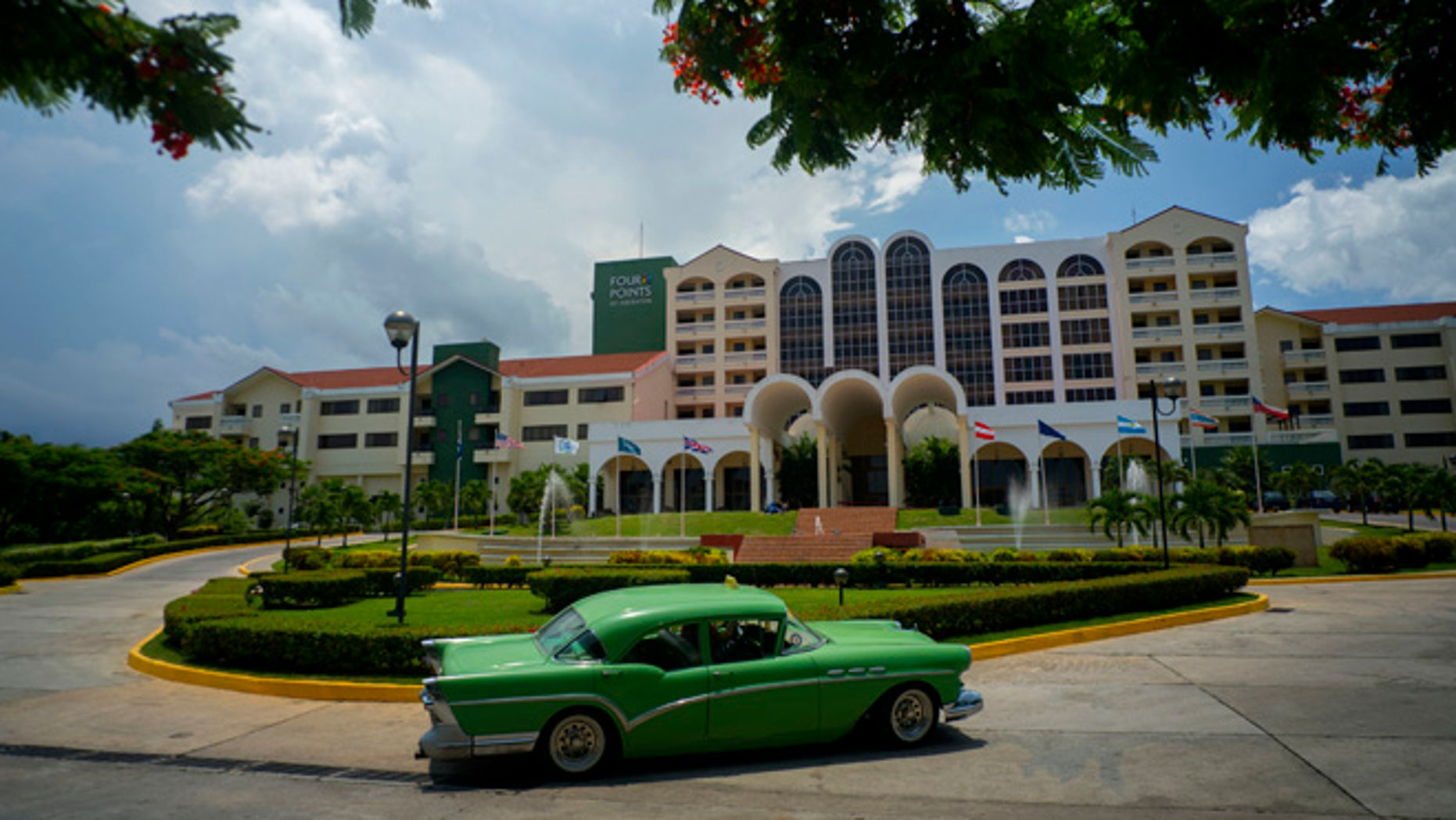 A vintage car passes in front of the Four Points by Sheraton hotel in Havana, Tuesday, June 28, 2016.