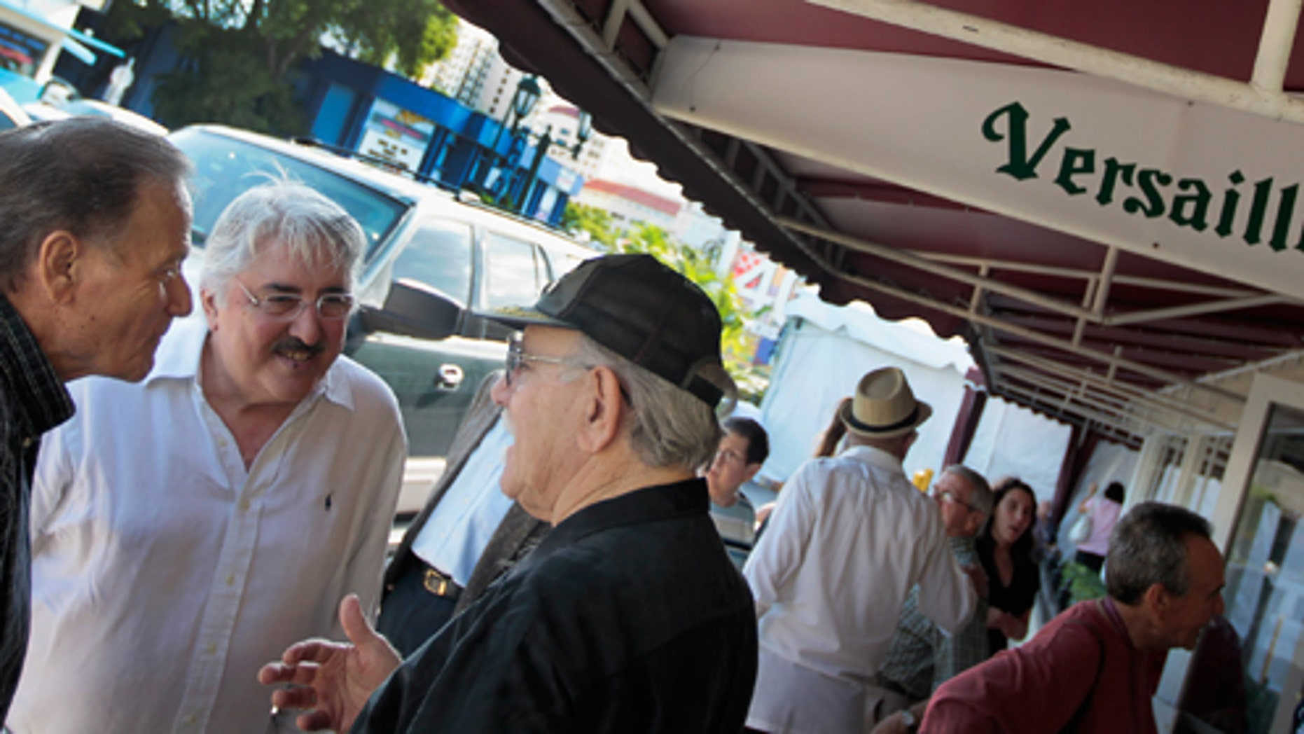 MIAMI, FL - JULY 12:  People gather in front of Versailles restaurant during the Cuban restaurants 40th anniversary party on July 12, 2011 in Miami, Florida. The famous restaurant was founded by a Cuban exile and is where people hang out to discuss politics over a Cuban coffee and to see which U.S. president, governors, legislators, mayors and commissioners pass through to court the Cuban vote.  (Photo by Joe Raedle/Getty Images)
