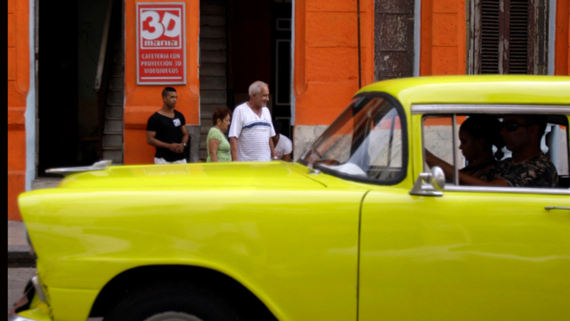 """A classic American car that is used as a taxi passes by the entrance of a private movie theater called """"3D Mania"""" in Havana, Cuba, Monday, Oct. 28, 2013. Cuban entrepreneurs have quietly opened dozens of backroom video salons over the last year, seizing on ambiguities in licensing laws to transform cafes and childrenâs entertainment parlors into a new breed of private business unforeseen by recent official openings in the communist economy. (AP Photo/Franklin Reyes)"""