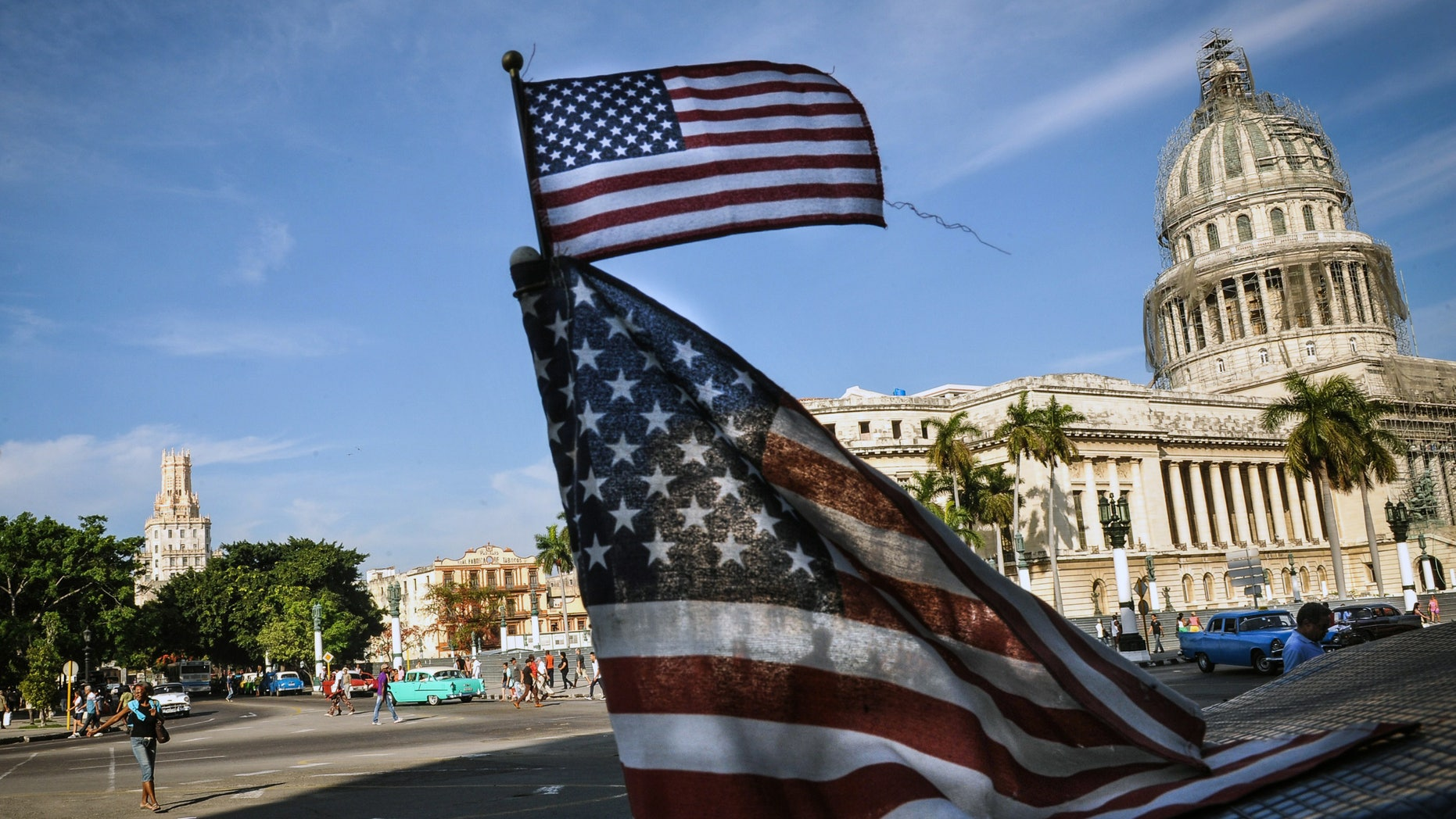 """US flags are seen in a bici-taxi near the capitol in Havana on January 23, 2015. Hours into historic US-Cuba talks in Havana, a Cuban official came out to boast about the """"relaxed"""" atmosphere at the meeting between the old Cold War adversaries. After barely speaking face-to-face since the 1960s, the United States and Cuba took big steps toward normalizing ties by holding a two-day meeting, even though the talks highlighted enduring rifts between the nations. AFP PHOTO / Yamil LAGE        (Photo credit should read YAMIL LAGE/AFP/Getty Images)"""