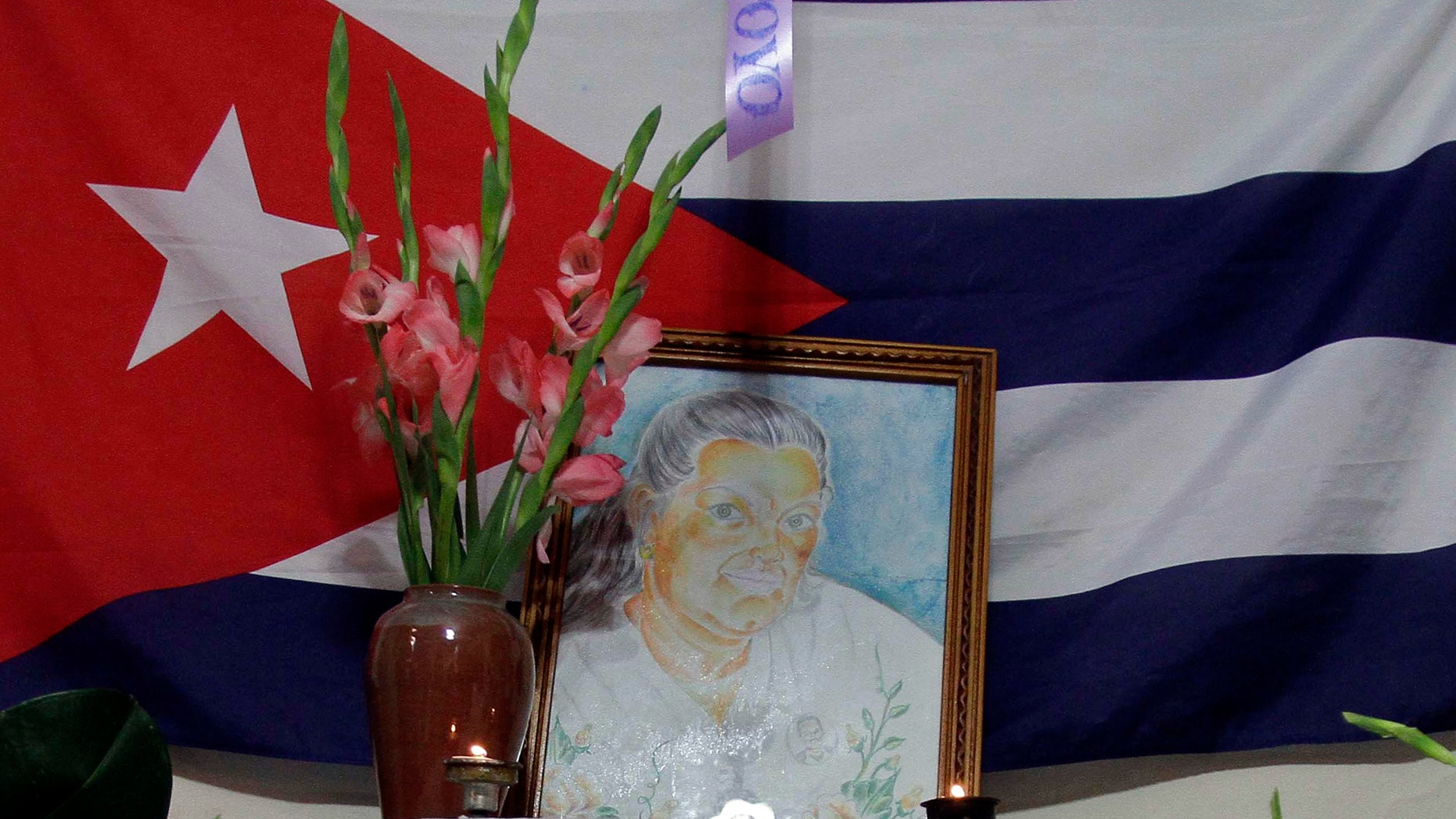 """A painting of Laura Pollan, late leader of the dissident group """"Ladies in White,"""" is flanked by flowers, candles and a Cuban flag during a gathering in her honor at her home in Havana, Cuba, Saturday Oct. 15, 2011. According to Elizardo Sanchez, head of the Cuban Commission for Human Rights and National Reconciliation, Pollan died of a cardio-respiratory attack on Friday Oct. 14, 2011. (AP Photo/Franklin Reyes)"""
