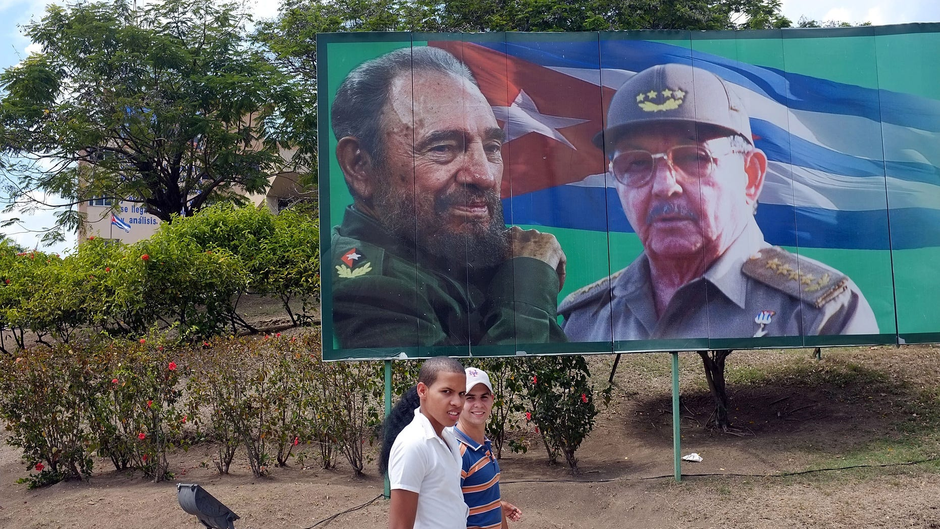 SANTIAGO DE CUBA, CUBA - MARCH 27:  Two teens walk by a billboard of Fidel and Raul Castro a day after Pope Benedict XVI held a historic mass in the city on March 27, 2012 in Santiago de Cuba. Fourteen years after Pope John Paul II visited Cuba, Pope Benedict is making his first trip to the communist country. Benedict, who arrived from Mexico, conducted a mass in the city of Santiago de Cuba first followed by a mass in Havana before leaving on the 28th. Tensions are high in Cuba between dissidents and the government as activists hope the international exposure of the Papal visit will result in renewed attention to their struggle for greater freedoms.  (Photo by Spencer Platt/Getty Images)