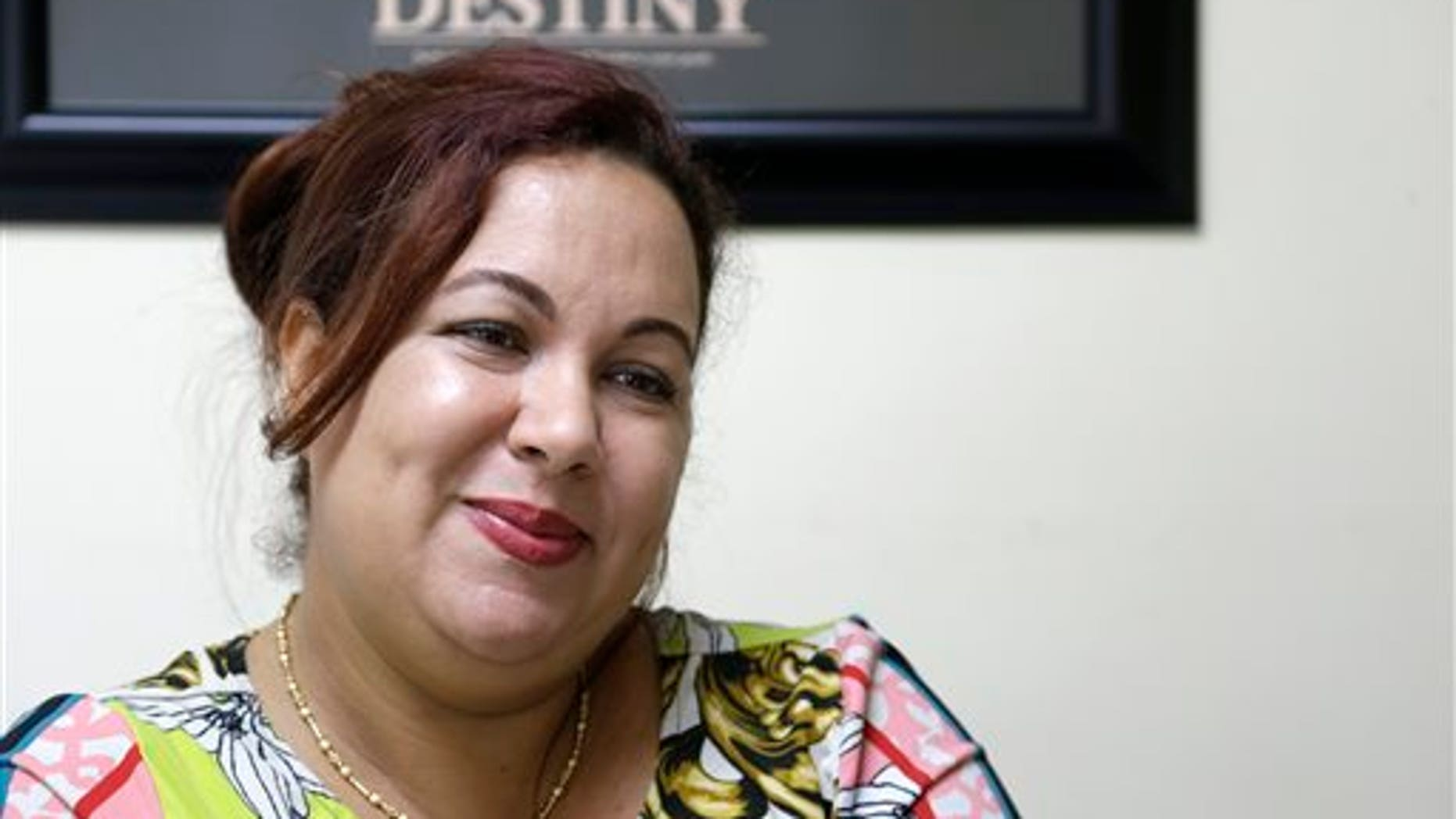 In this Sept. 19, 2013 photo, Irka Ducasse Blanes, a recent Cuban immigrant, smiles during an interview at a tax preparation office where she works in Miami. Since 2002, the number of Cubans leaving has hovered around 30,000 annually, making the last 10 years the largest exodus since the start of the revolution. The influx of new arrivals is evident throughout Miami, the heart of Cubas exile population. (AP Photo/Wilfredo Lee)