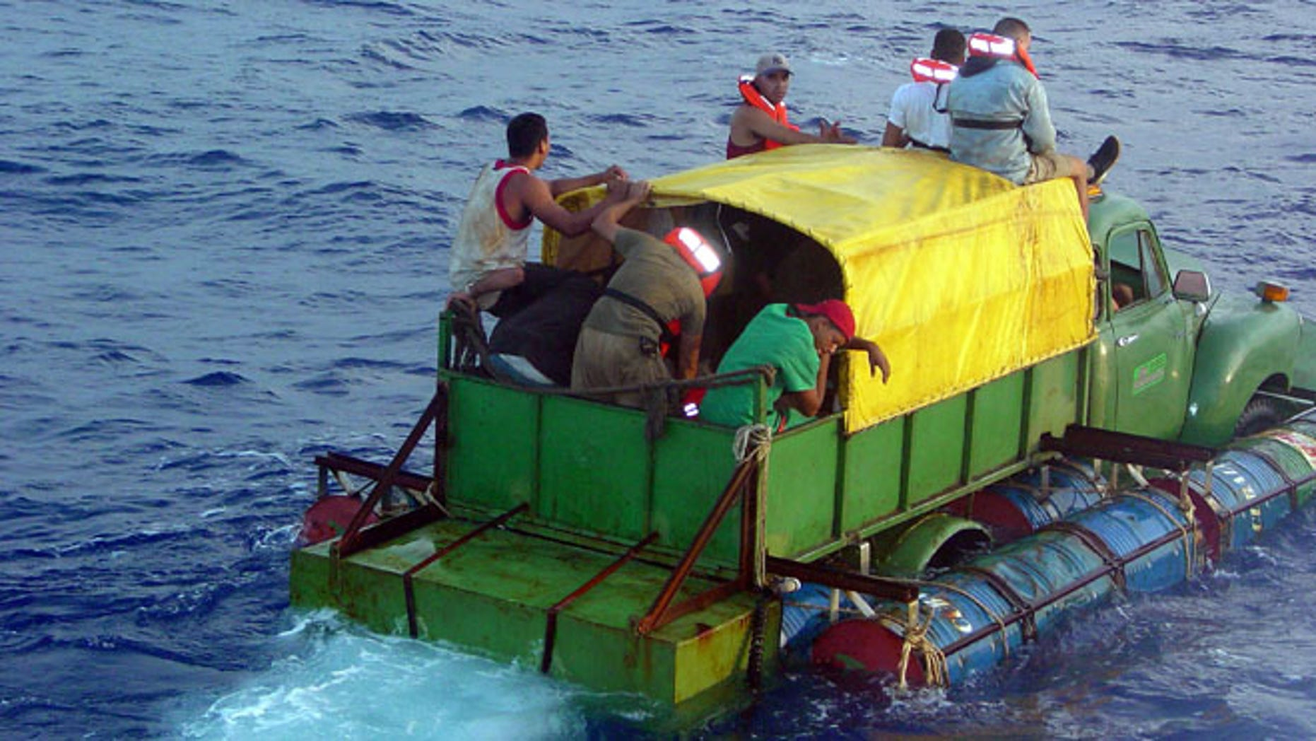 AT SEA - JULY 24:  In this U.S. Coast Guard handout, Cuban migrants trying to reach the U.S. coast in Florida ride a makeshift boat made out of a 1951 Chevrolet truck with a propeller driven off the drive shaft July 16, 2003 off the coast of Florida. The U.S. Coast Guard Cutter Key Largo returned the12 Cuban migrants from the vessel back to Cuba after making it within 40 miles of Key West, Florida. The photograph was released a week after the crew was repatriated.  (Photo by Gregory Ewald/ U.S. Coast Guard/ Getty Images)
