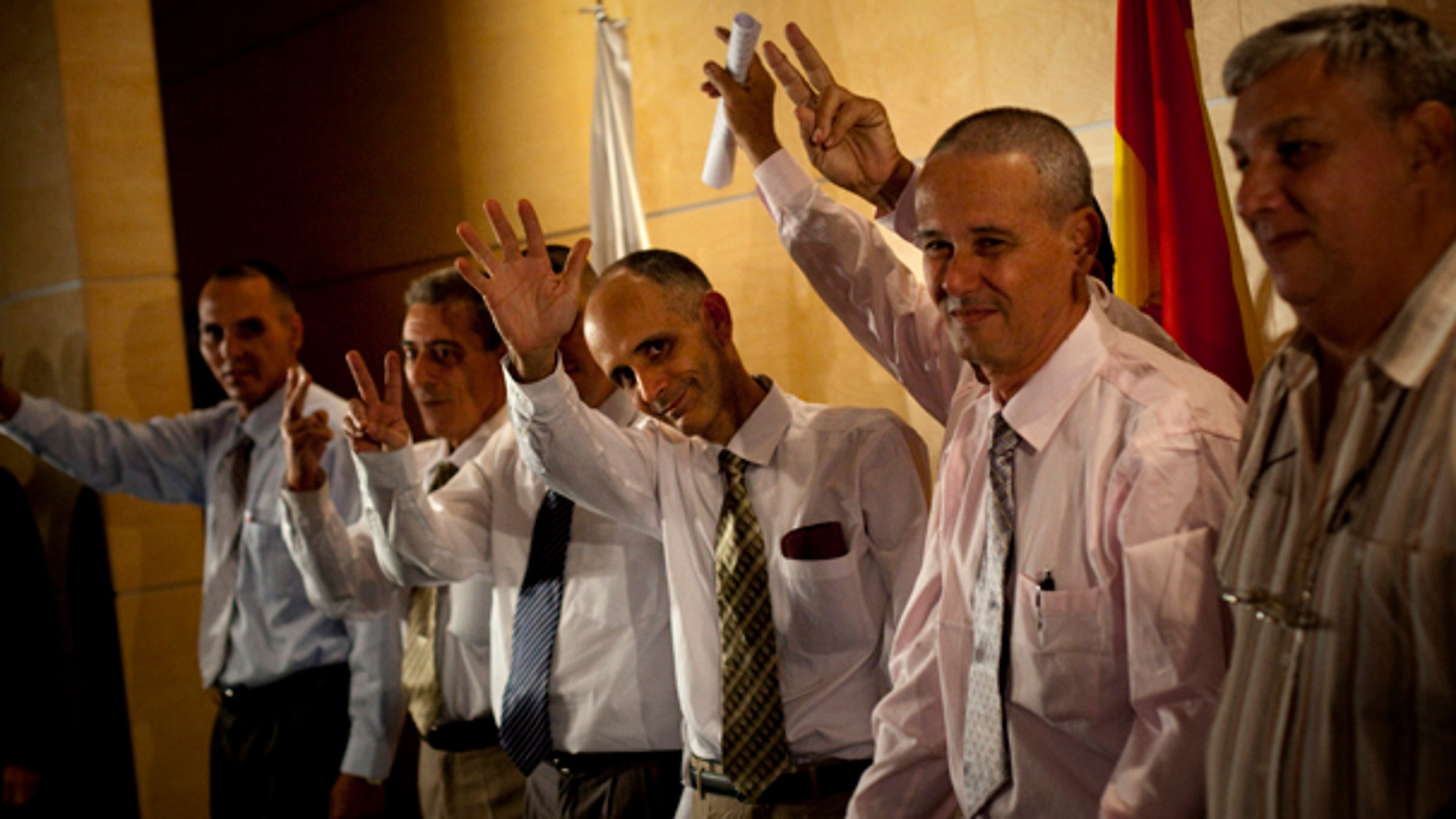 July 13: Cuban dissidents wave for press photographers upon the arrival at Madrid's Barajas airport.  Seven Cuban political prisoners and members of their families arrived in Madrid on Tuesday, the first of a group of inmates the government in Havana has promised to release, an official said. (AP)