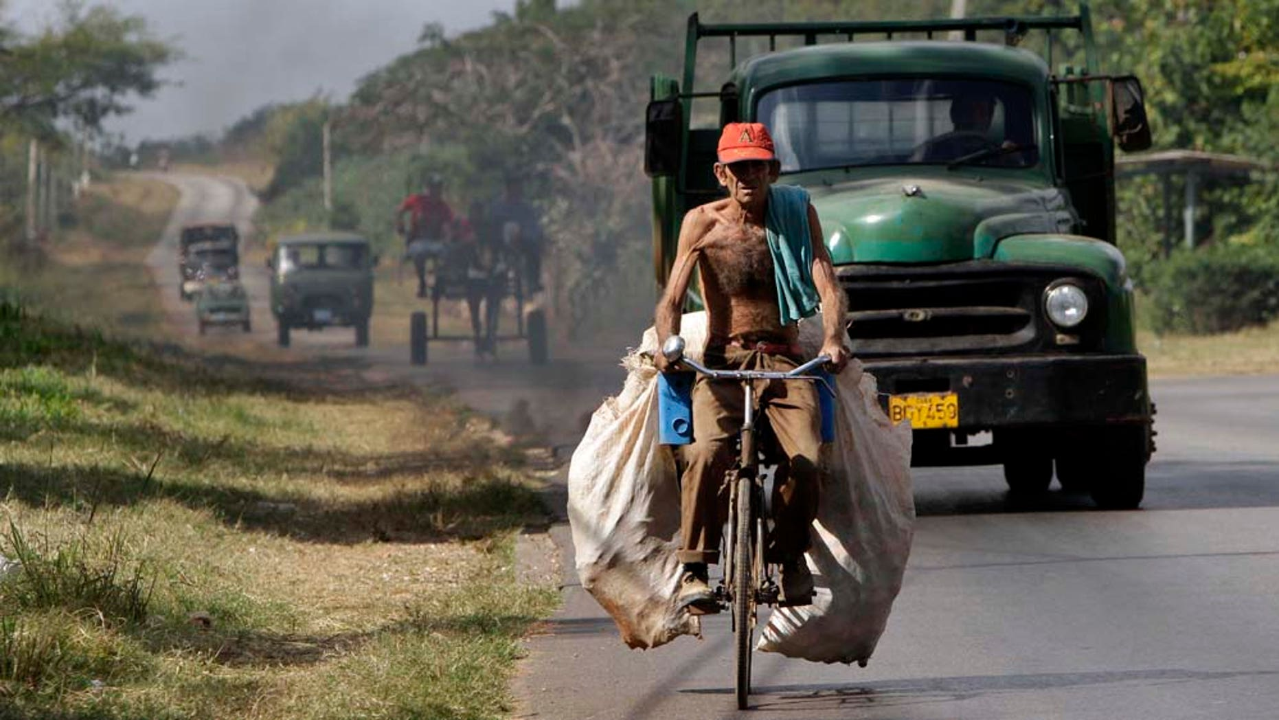 A man carries sacks with beer cans to recycle on his bicycle in Havana, Cuba, Thursday, Jan. 6, 2011. (AP Photo/Franklin Reyes)