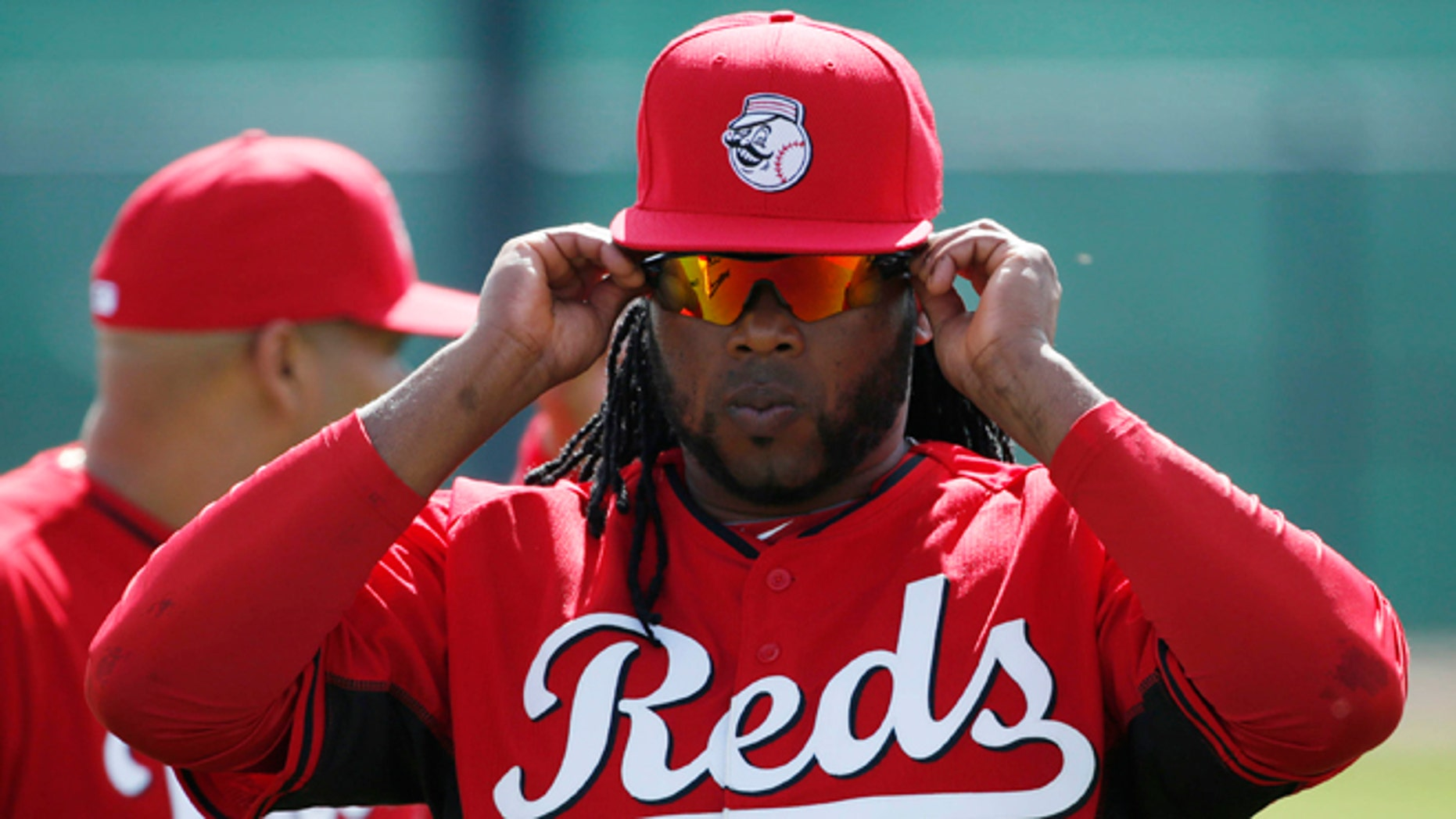 Cincinnati Reds' player Johnny Cueto adjusts his sunglasses during the team's first day of spring training practice Thursday, Feb. 19, 2015, in Goodyear, Ariz. (AP Photo/John Locher)