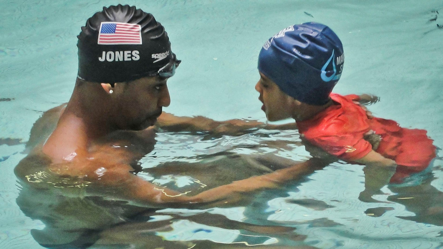 """Olympic gold medalist Cullen Jones give swimming lessons to Niko Diop, a pre-kindergarden student at Harlem's P.S. 125 in New York.  Jones is ambassador for the 5th Annual USA Swimming Foundation's """"Make a Splash Tour,"""" providing free swimming lessons, water safety education and awareness at city pools.  (AP Photo/Simone Smalls PR)"""