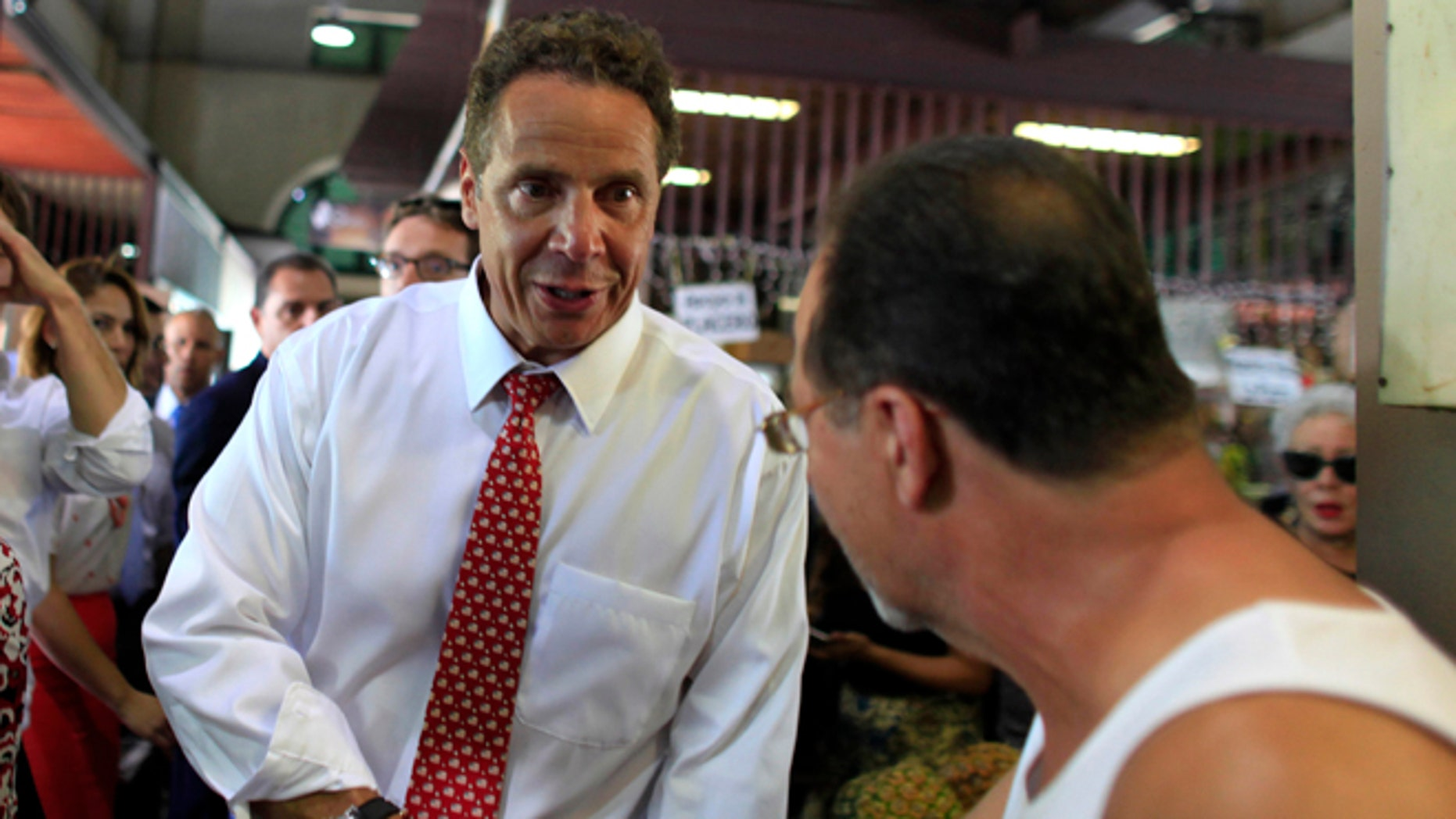 New York Gov. Andrew Cuomo greets a bystander during a visit to a local market in San Juan, Puerto Rico, Tuesday, Sept. 8, 2015. Cuomo and a delegation of top state officials met with Puerto Rico's Gov. Alejandro Garcia Padilla, pictured left, on Tuesday to develop what he called a historic partnership with the U.S. territory to help it emerge from a deepening economic crisis. (AP Photo/Ricardo Arduengo)